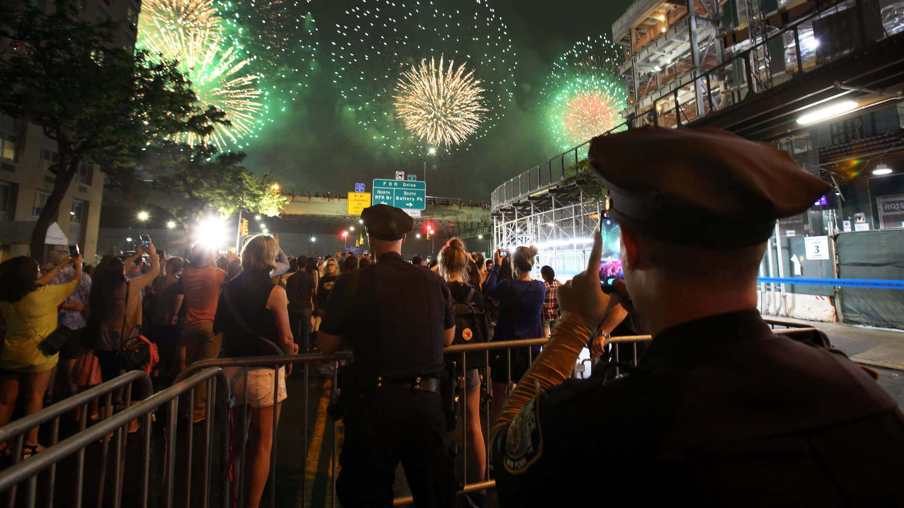 A New York City police officer takes a picture with his phone as he watches over spectators watching the Fourth of July fireworks, Monday, July 4, 2016, along the East River on the FDR Drive in New York.