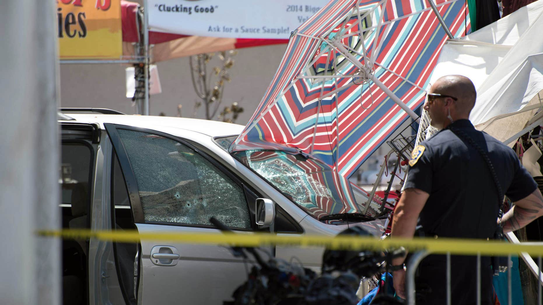 A Reno police officer stands guard at the scene after a minivan crashed into a vendor's tent at the Biggest Little City Wing Fest in downtown Reno, Nev.