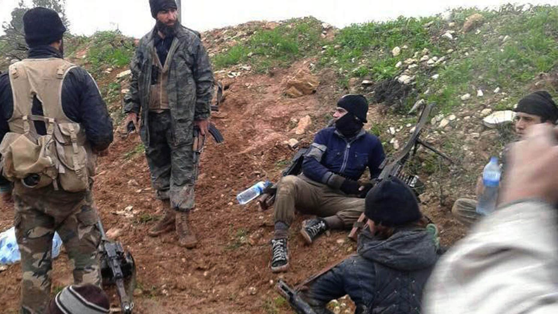 FILE - In this Dec. 14, 2014 file photo provided by the anti-government activist group Syrian Observatory for Human Rights, which has been authenticated based on its contents and other AP reporting, shows fighters from the Al Qaeda-linked Nusra Front and other rebel factions resting after clashes with Syrian troops in Wadi Deif in the northwestern province of Idlib, Syria.