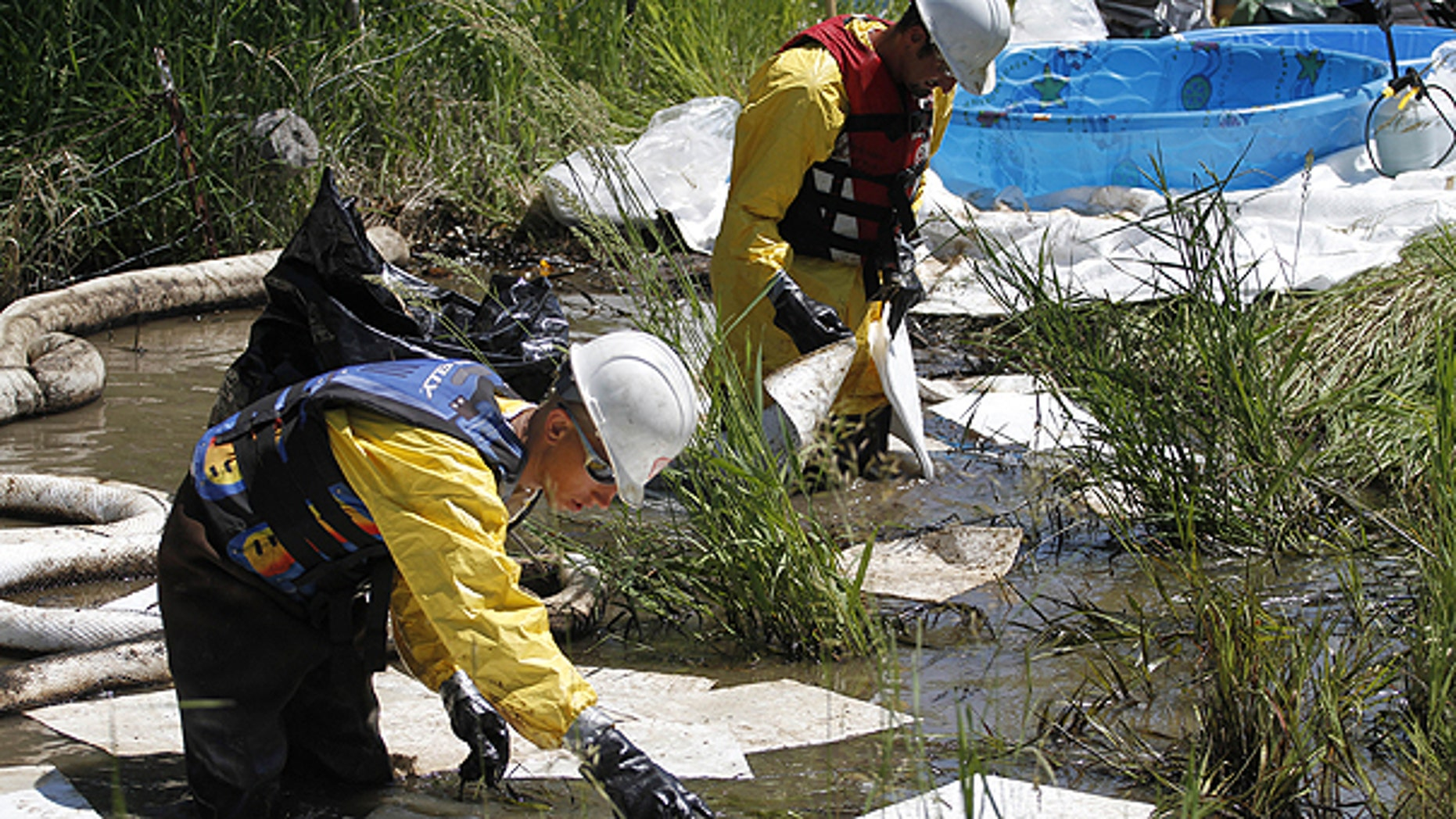 July 5: Cleanup crews work to clear oil from along side the Yellowstone River in Laurel, Mont.