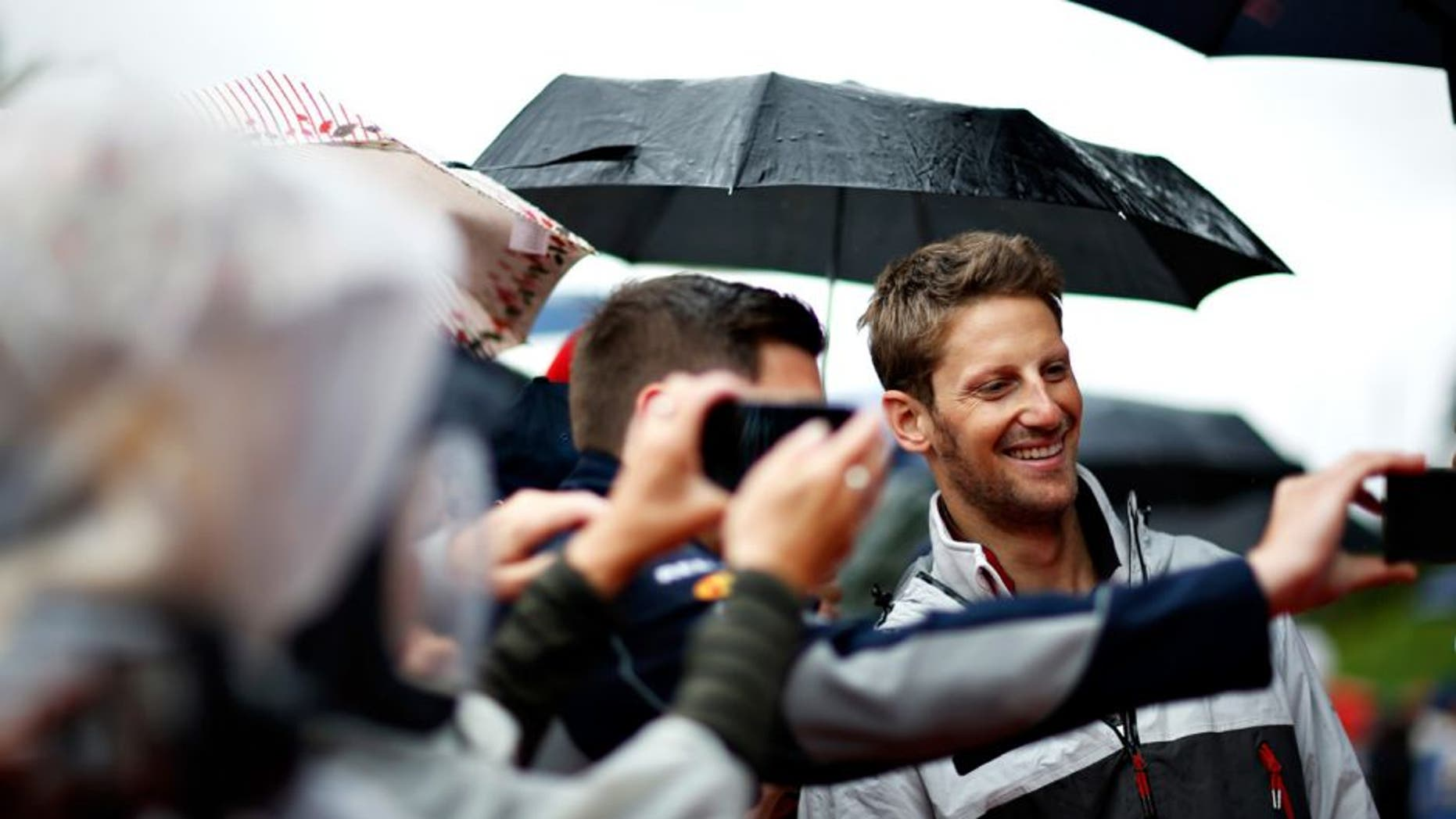 SPIELBERG, AUSTRIA - JULY 03: Romain Grosjean of France and Haas F1 poses for a photo with a fan before the Formula One Grand Prix of Austria at Red Bull Ring on July 3, 2016 in Spielberg, Austria. (Photo by Charles Coates/Getty Images)