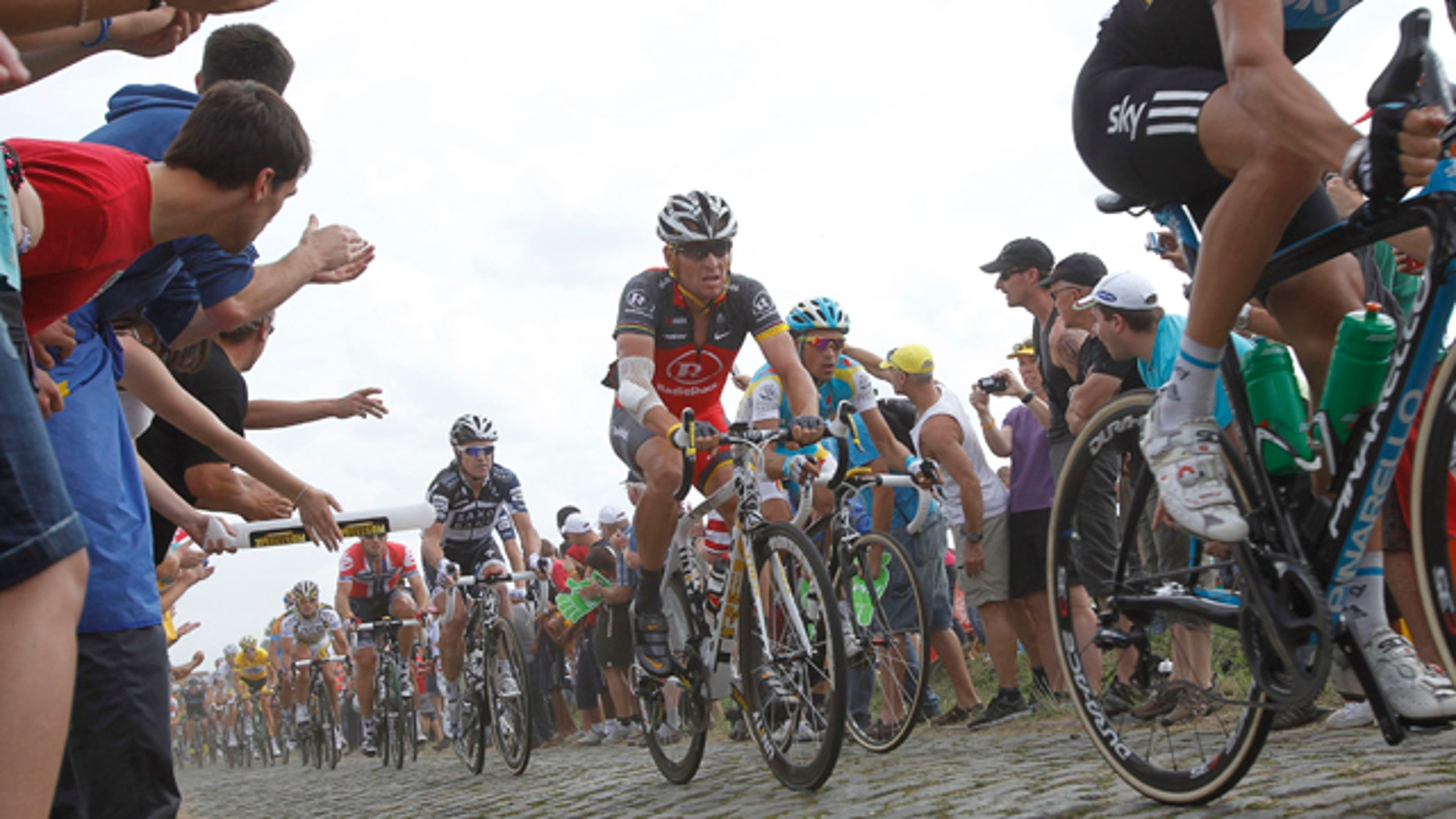 July 6: Lance Armstrong, center, and Alberto Contador of Spain, right of Armstrong, ride on a cobblestone section during the third stage of the Tour de France cycling race over 132.4 miles with start in Wanze, Belgium and finish in Arenberg, France.