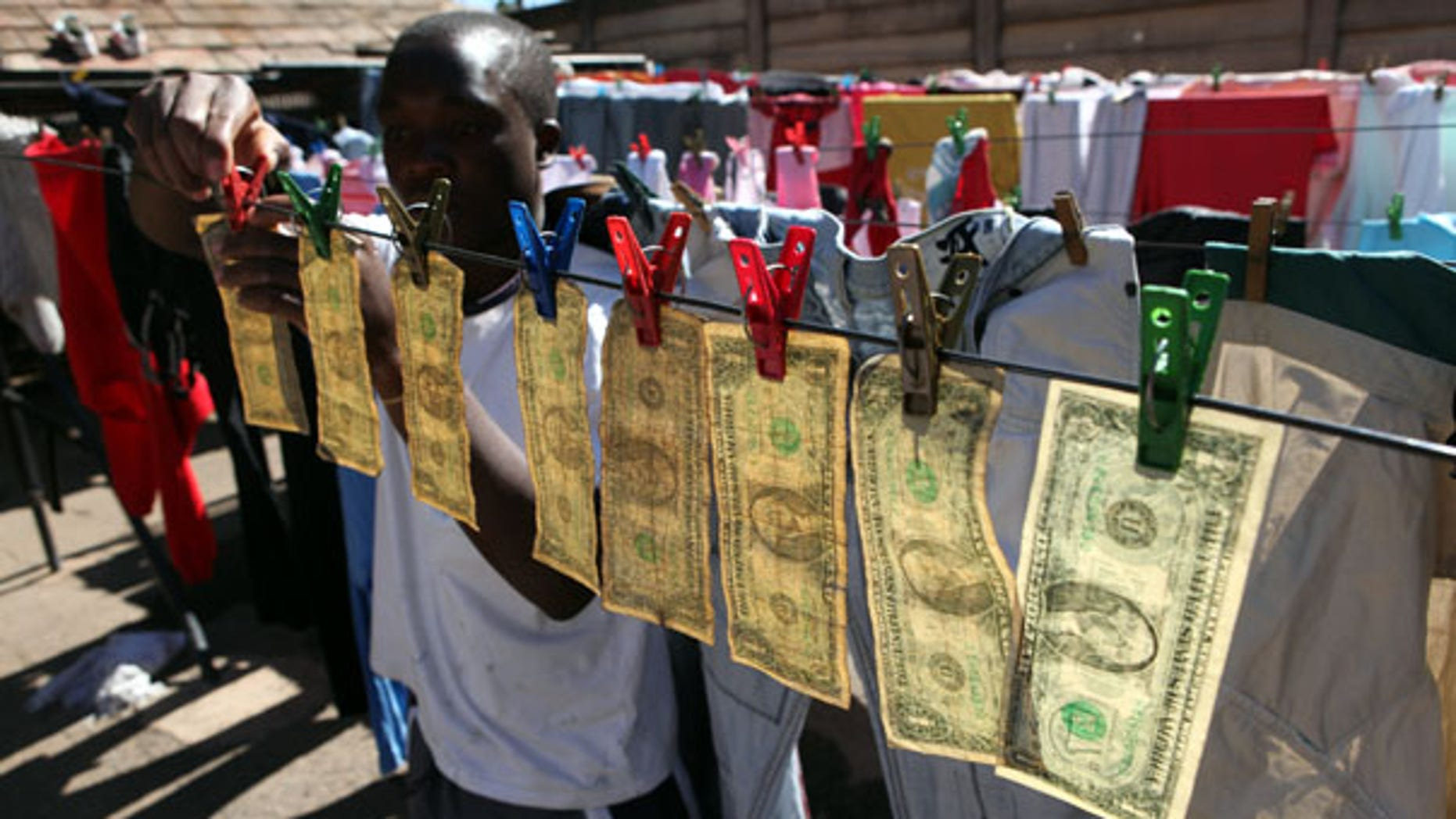 July 6: Alex Mupondi hangs dollar bills on a drying line after washing them in Harare -- Zimbabwe's style of laundering dirty money.