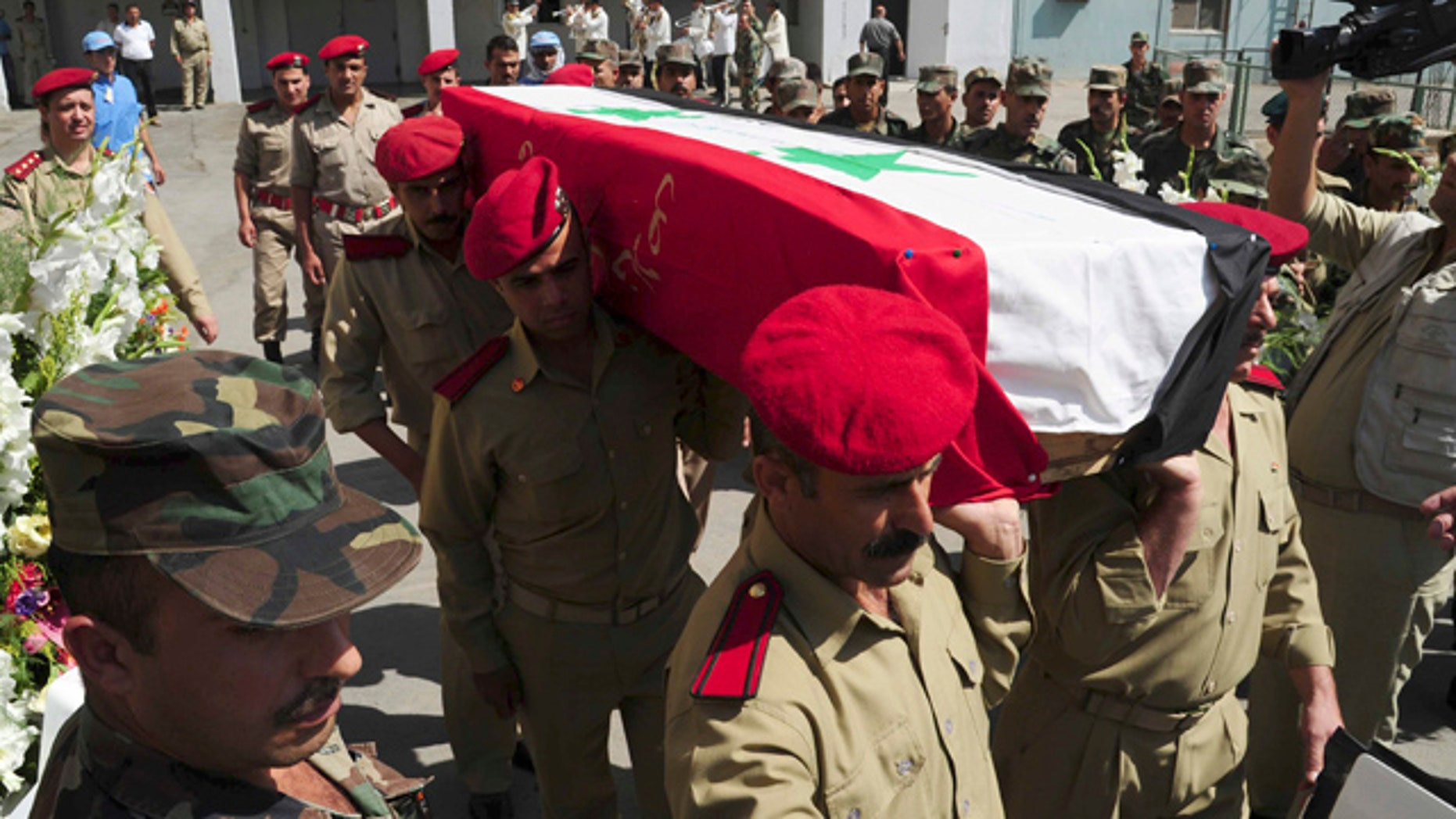 July 6: In this photo released by the Syrian official news agency SANA, Syrian soldiers carry the coffin of a comrade who was killed in recent violence in the country during his funeral procession at a hospital in Damascus, Syria.