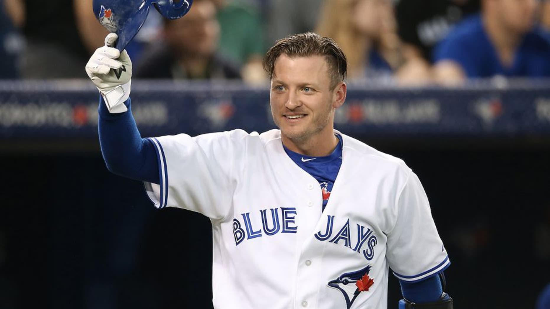 TORONTO, CANADA - JUNE 8: Josh Donaldson #20 of the Toronto Blue Jays greets a member of the Miami Marlins as he tips his helmet during MLB game action against the Miami Marlins on June 8, 2015 at Rogers Centre in Toronto, Ontario, Canada. (Photo by Tom Szczerbowski/Getty Images)