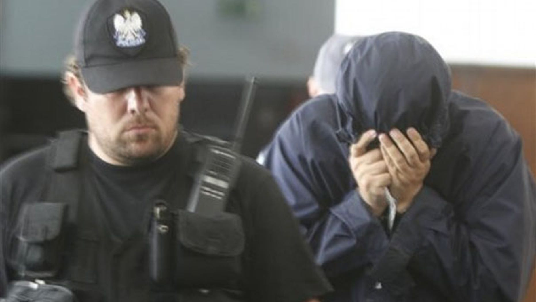 July 5: Hiding his face, Israeli citizen Uri Brodsky is escorted by police officials to a court session in Warsaw.