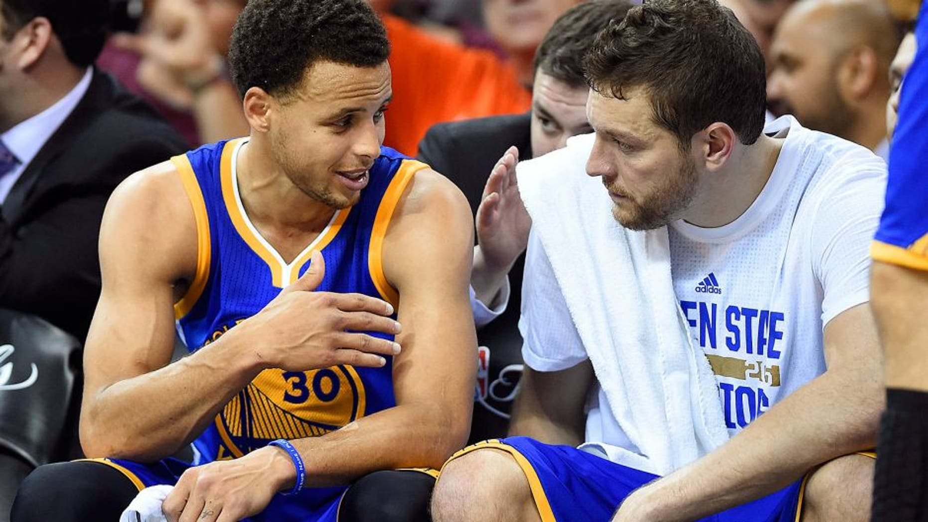 Jun 11, 2015; Cleveland, OH, USA; Golden State Warriors guard Stephen Curry (30) talks to forward David Lee (10) on the bench during the fourth quarter against the Cleveland Cavaliers in game four of the NBA Finals at Quicken Loans Arena. Mandatory Credit: Bob Donnan-USA TODAY Sports