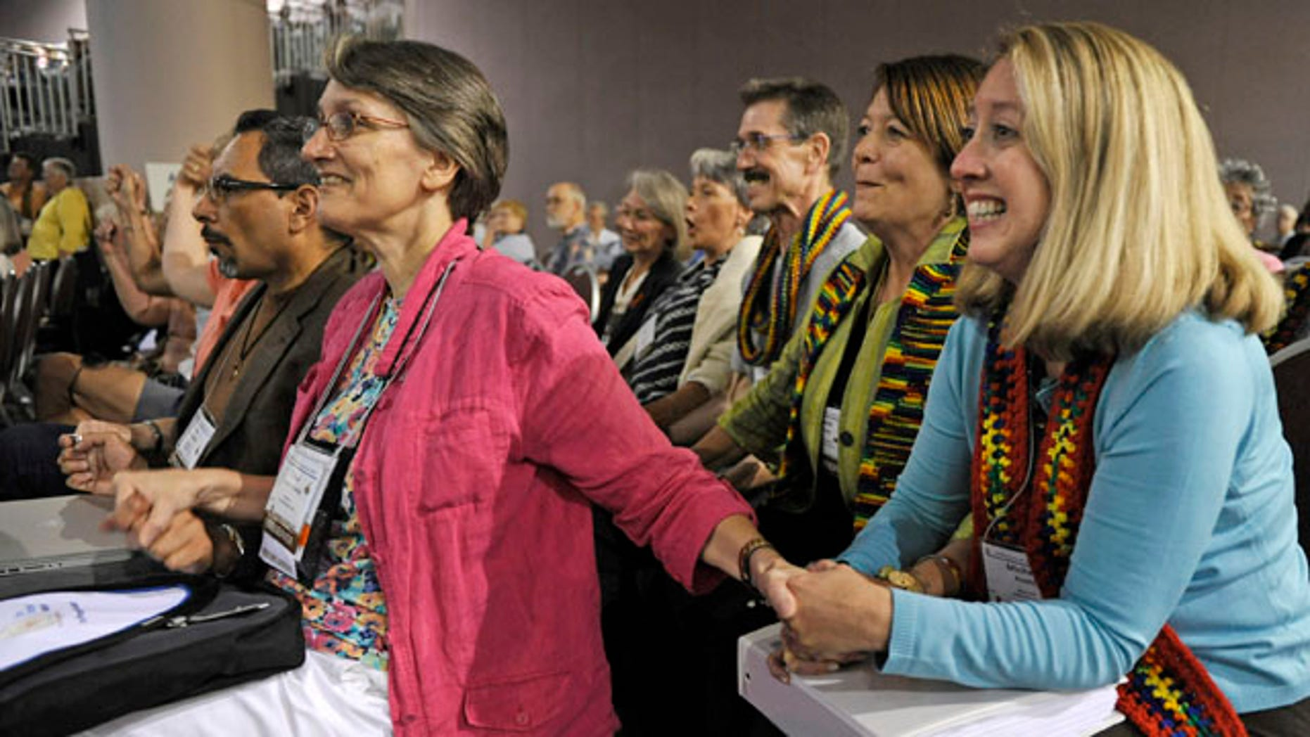 July 8: Observers Tricia Dykes Koenig, left, and Michelle Ready, right, smile as the General Assembly of the Presbyterian Church meeting in Minneapolis votes to approve lifting the churches ban on ordaining non-celebrate gays and lesbians as clergy.