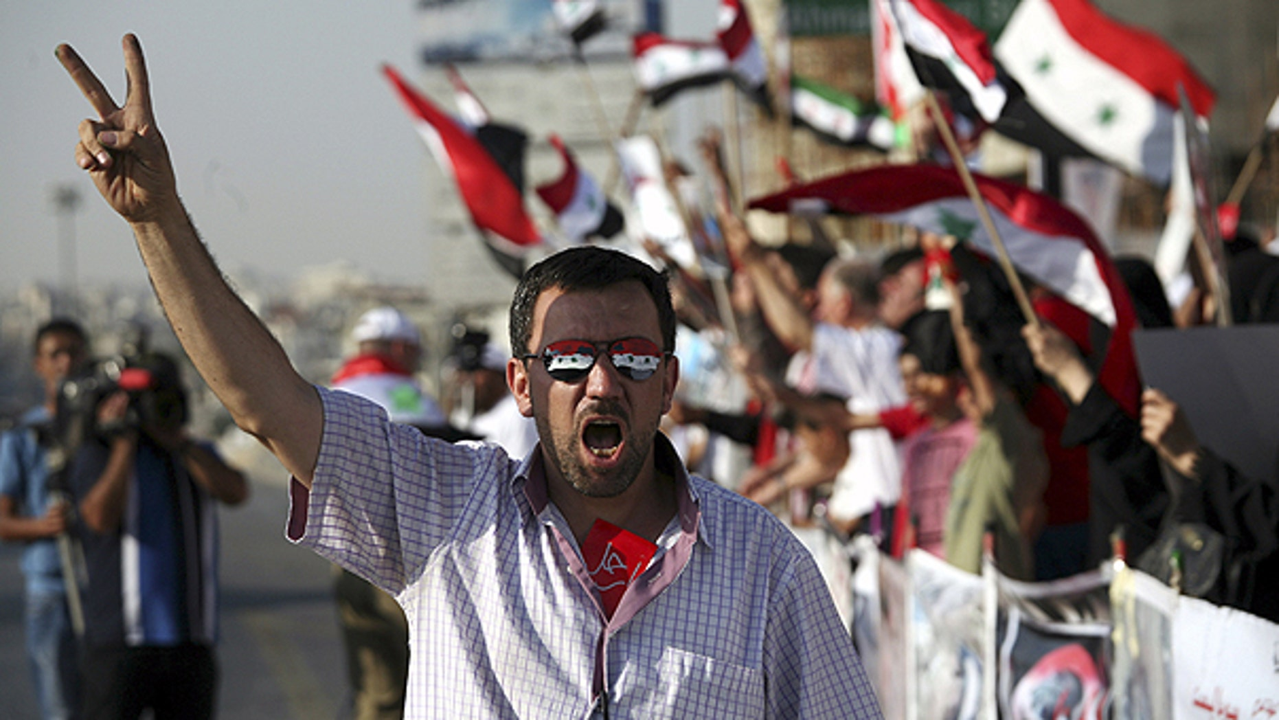 July 7: A man wearing sunglasses painted with the colors of the Syrian national flag gives a v-sign during a rally in support of the Syrian opposition in Amman, Jordan.