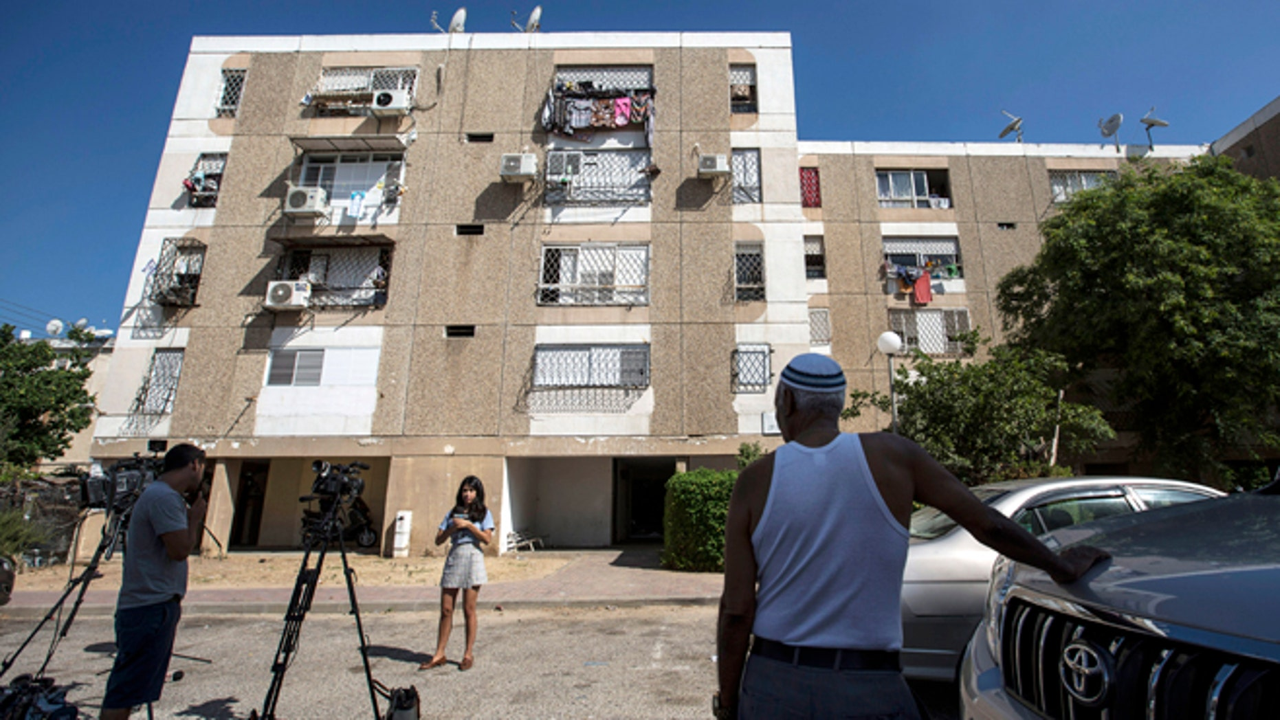 July 9, 2015: Israeli journalists report outside the apartment building of Ethiopian-Israeli Avraham Mengisto, 28, in the costal city of Ashkelon, Israel.