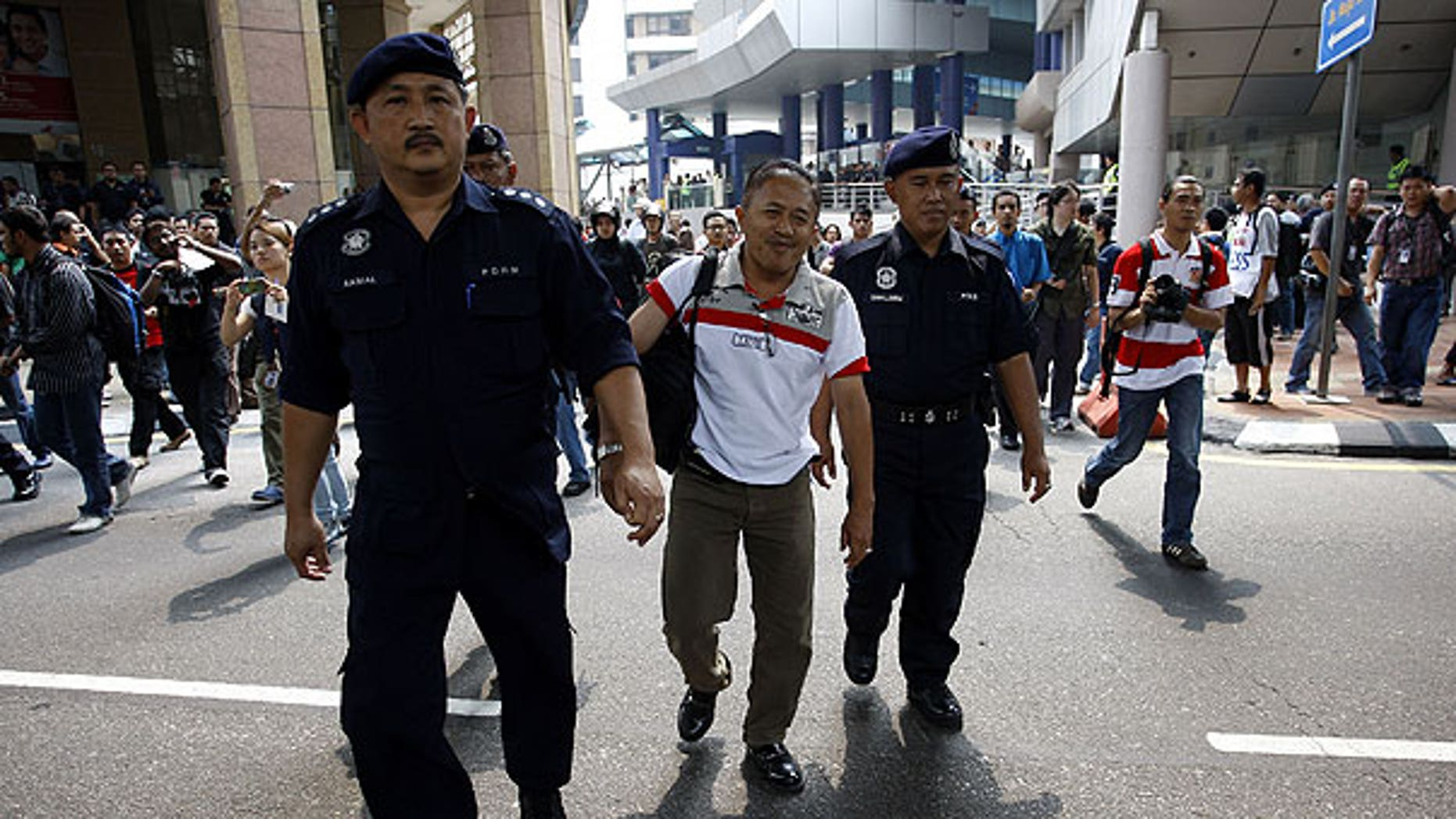 July 9: Malaysian police officers detain a man near Independence Square in Kuala Lumpur, Malaysia. Malaysian police said they have detained at least 644 people trying to assemble at a stadium for a banned rally seeking electoral reforms.