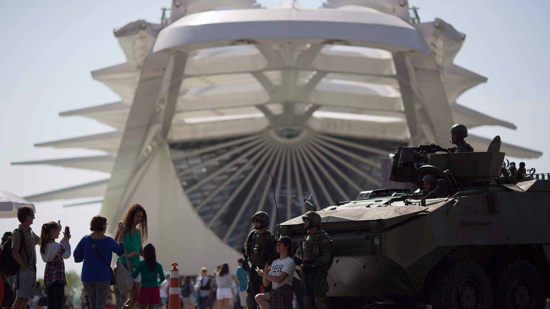 People take pictures with marines and their armored vehicle outside the Museum of Tomorrow in Rio de Janeiro, Brazil.