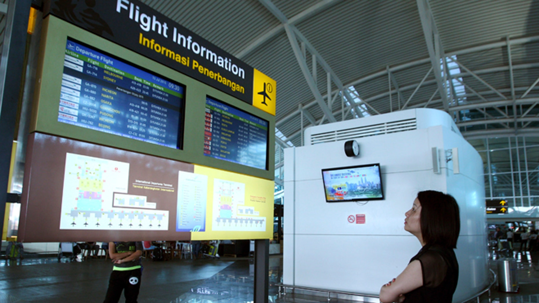 July 10, 2015: A traveler checks the status of flights at Bali's international airport, Indonesia.
