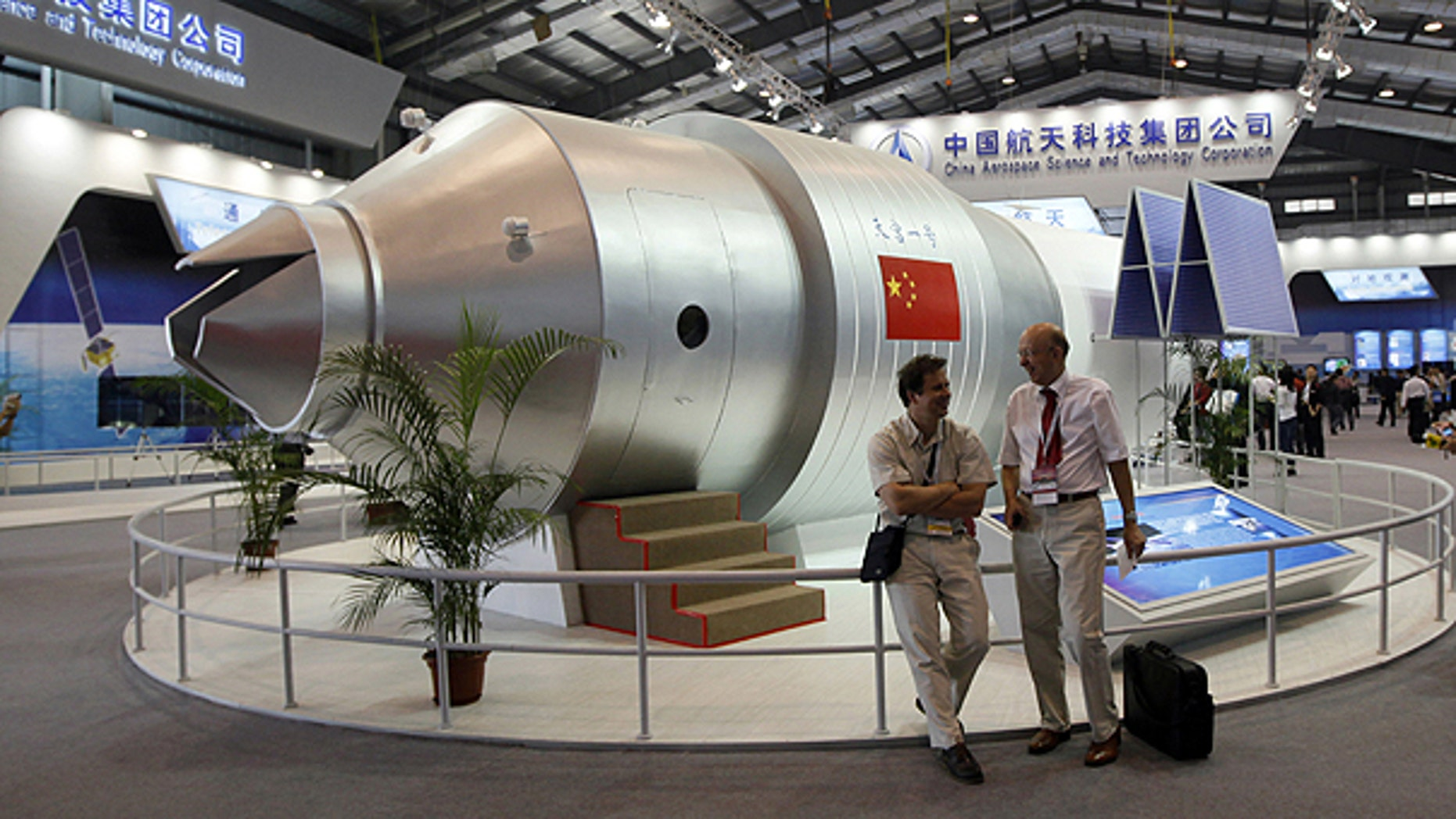 In this photo taken Nov. 16, 2010, visitors sit besides a model of Chinese made Tiangong 1 space station at the 8th China International Aviation and Aerospace Exhibition, known as Airshow China 2010, in Zhuhai city, south China, Guangdong province.