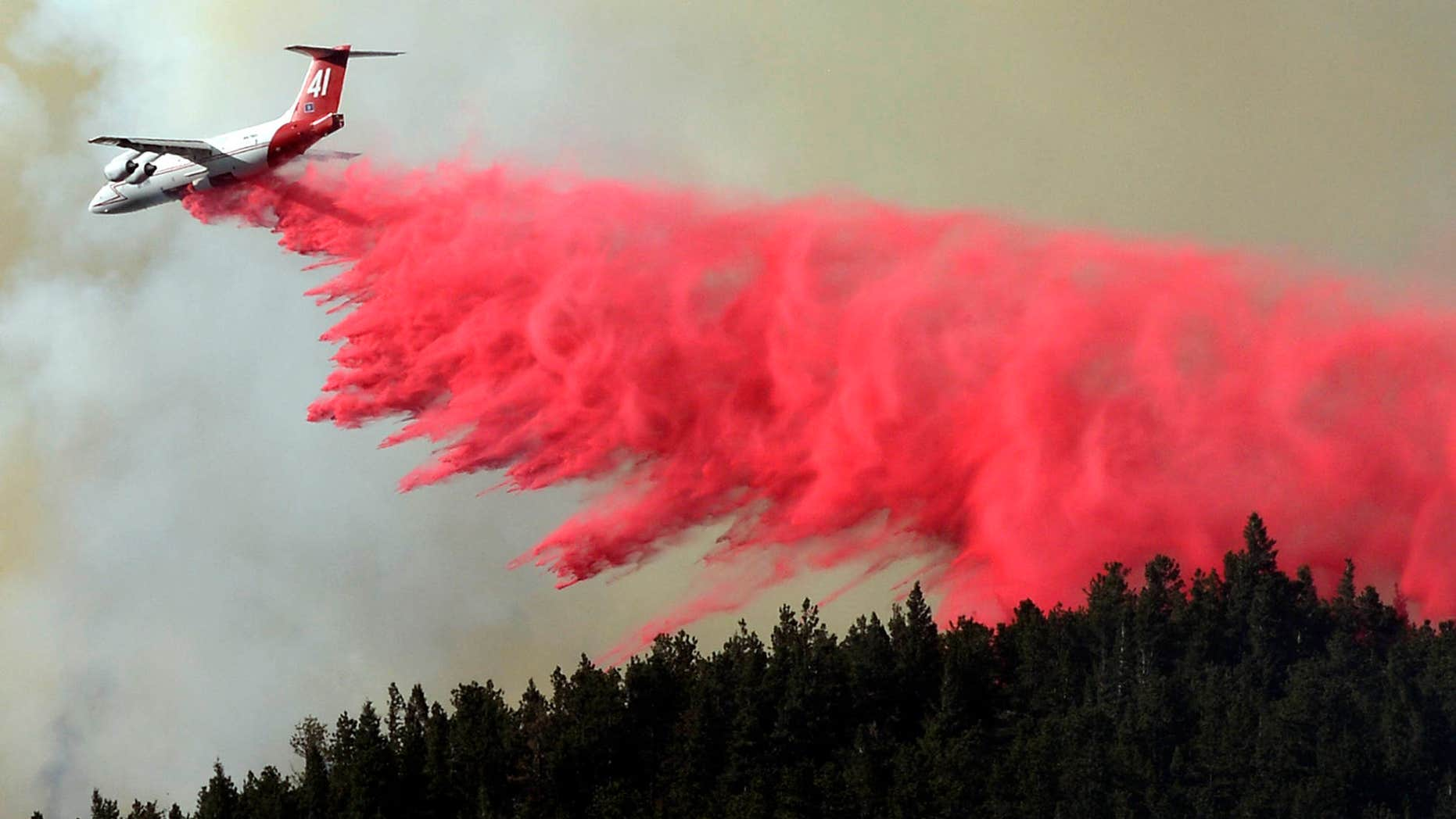 July 9, 2016: A trail of slurry is deposited by a bomber while fighting the Cold Springs Nederland fire in Colorado.