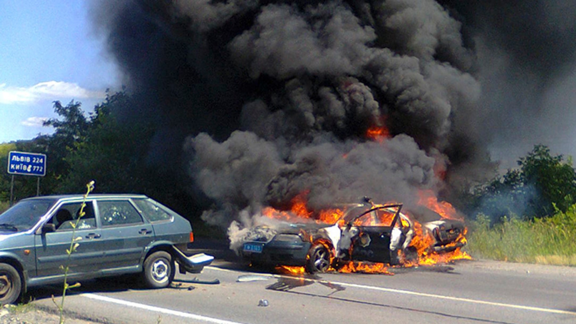 July 11, 2015: Two police cars on fire are seen at the site of unrest in Mukhachevo, Western Ukraine.