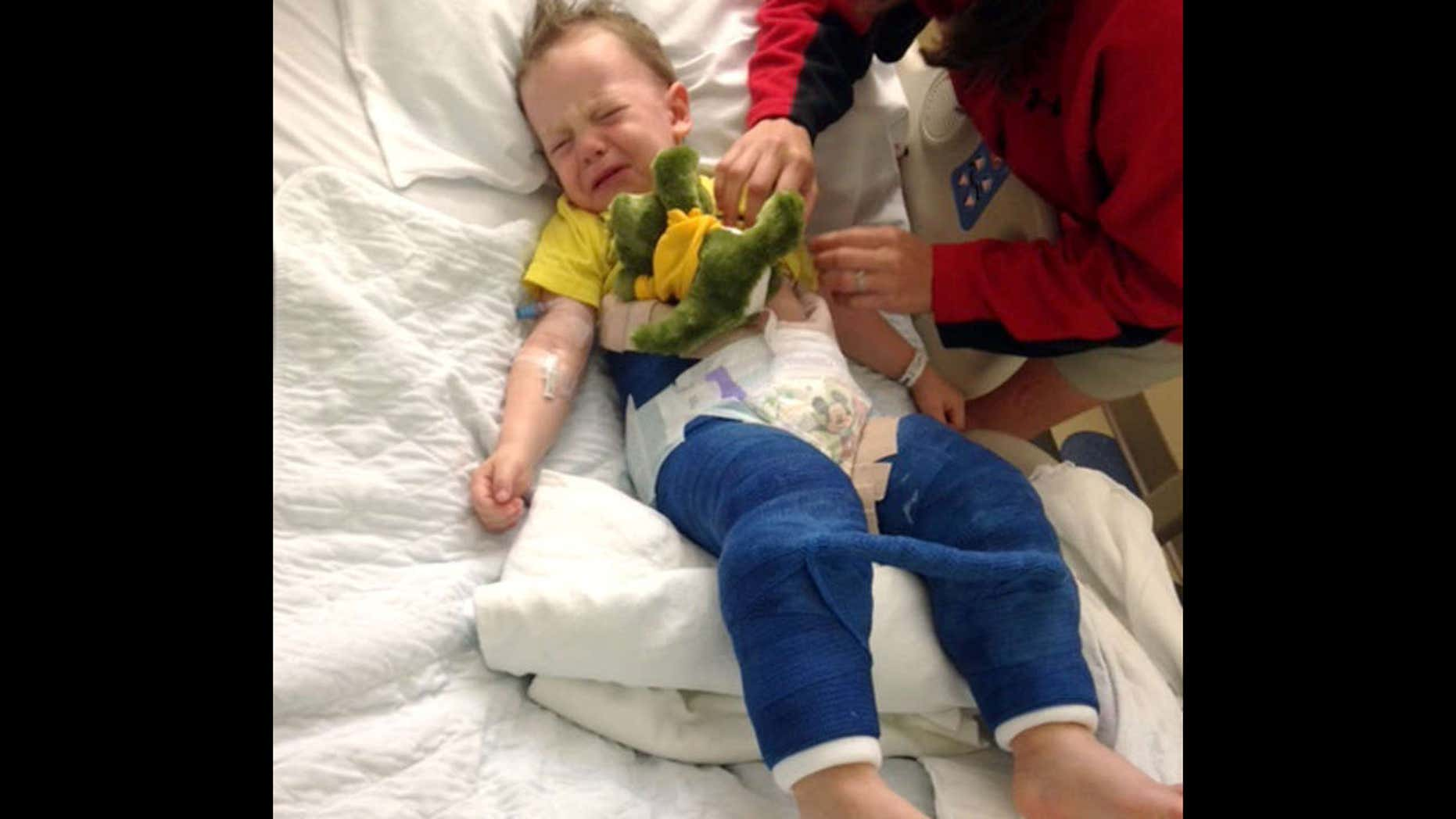 In this June 26, 2017 photo provided by Eddie Hill, Hill's son Colton is comforted while lying in a hospital bed at Johns Hopkins All Children's Hospital in St. Petersburg, Fla.
