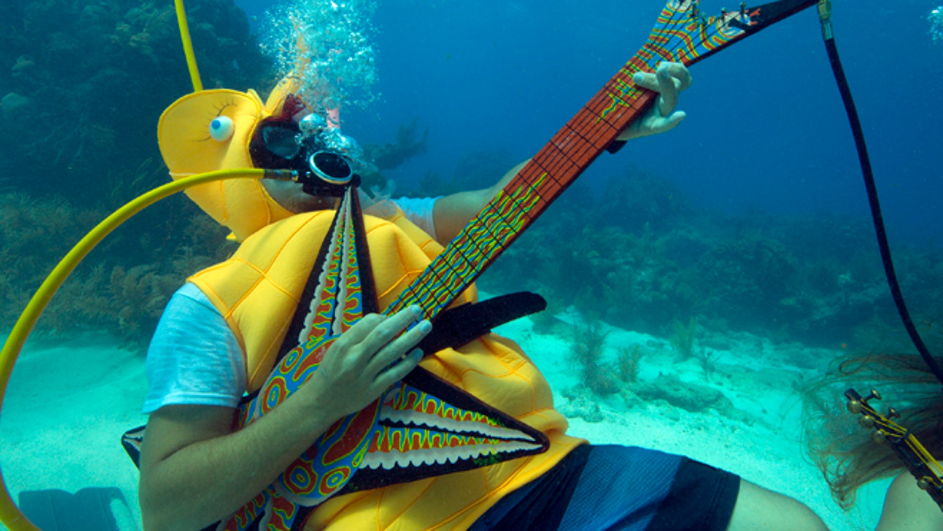 July 11, 2015: This photo provided by the Florida Keys News Bureau, Jeff Wright, costumed as a seahorse, rocks with a fake guitar during the Underwater Music Festival in the Florida Keys National Marine Sanctuary off Big Pine Key, Fla.