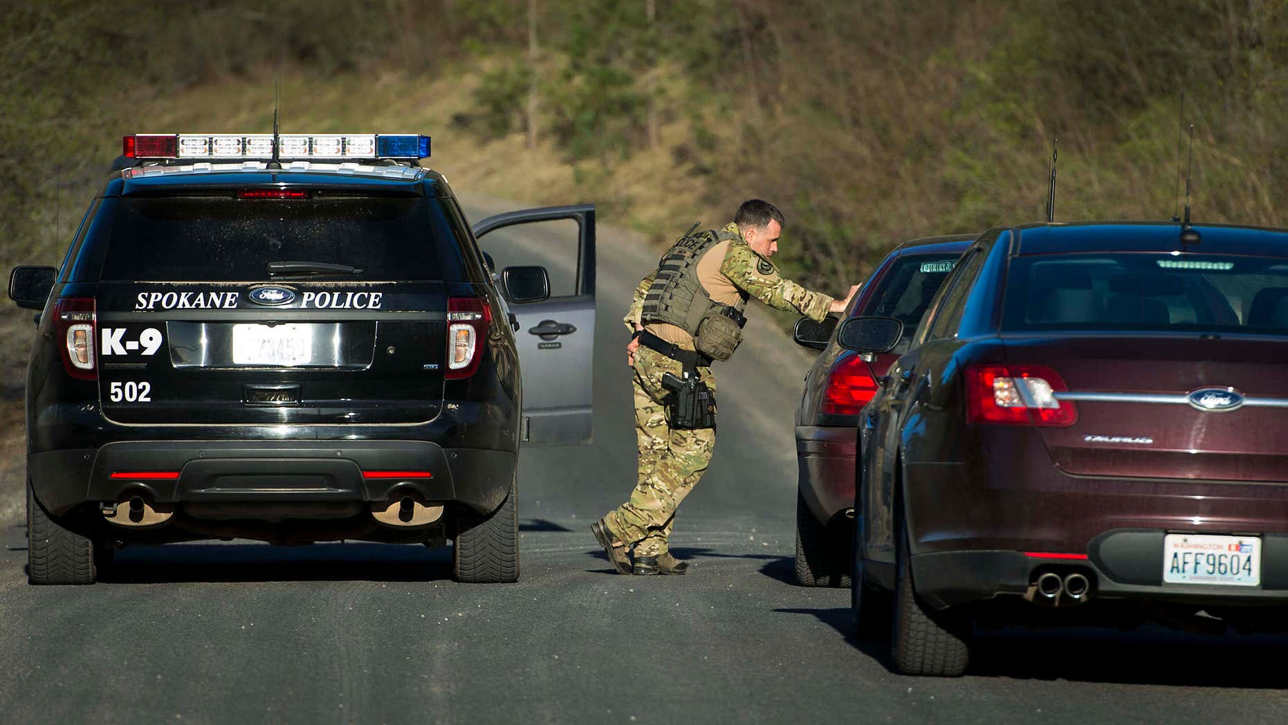 FILE - In this Thursday, April 7, 2016, file photo, officials stop vehicles as they search in Spokane Valley, Wash., for escaped mental patient Anthony Garver.