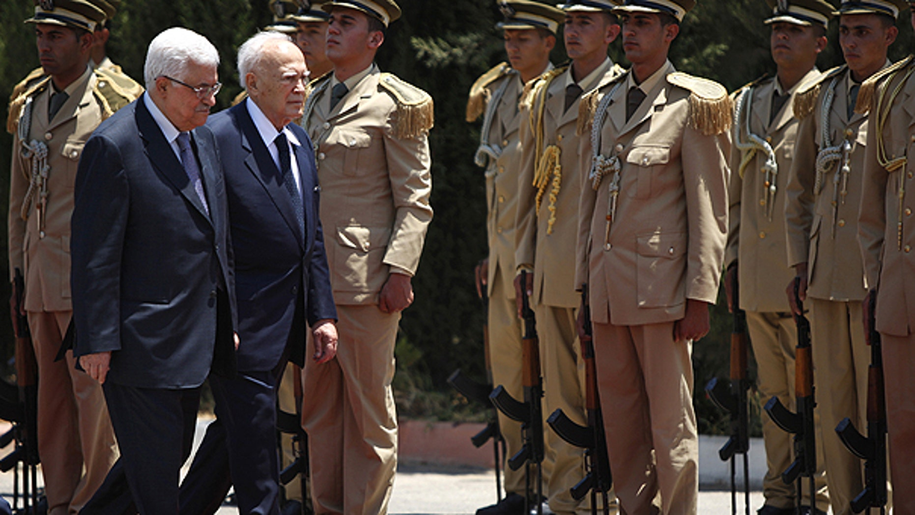 July 12: Palestinian President Mahmoud Abbas, left, and Greek President Karolos Papoulias review an honor guard prior their meeting in the West Bank city of Ramallah.
