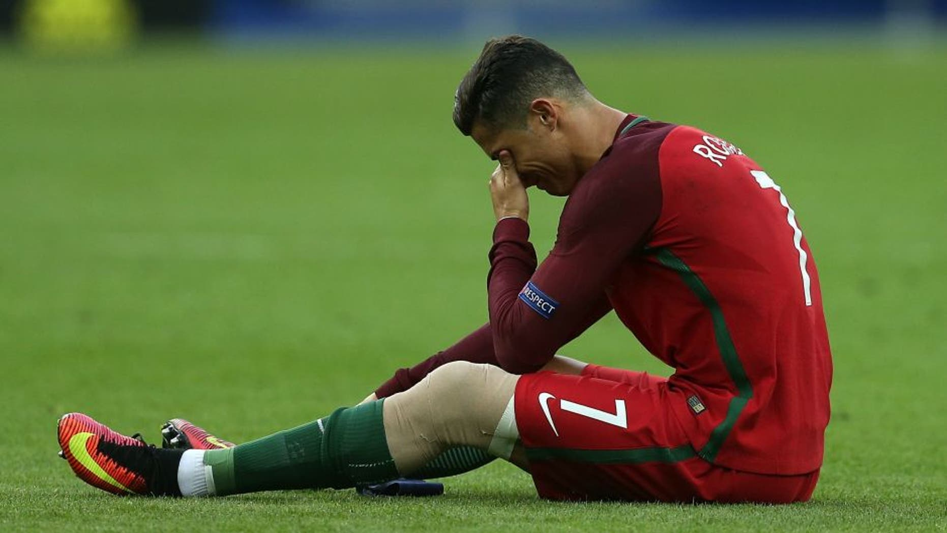 PARIS, FRANCE - JULY 10: Cristiano Ronaldo of Portugal lies injured during the UEFA Euro 2016 Final match between Portugal and France at Stade de France on July 10, 2016 in Paris, France. (Photo by Chris Brunskill Ltd/Getty Images)