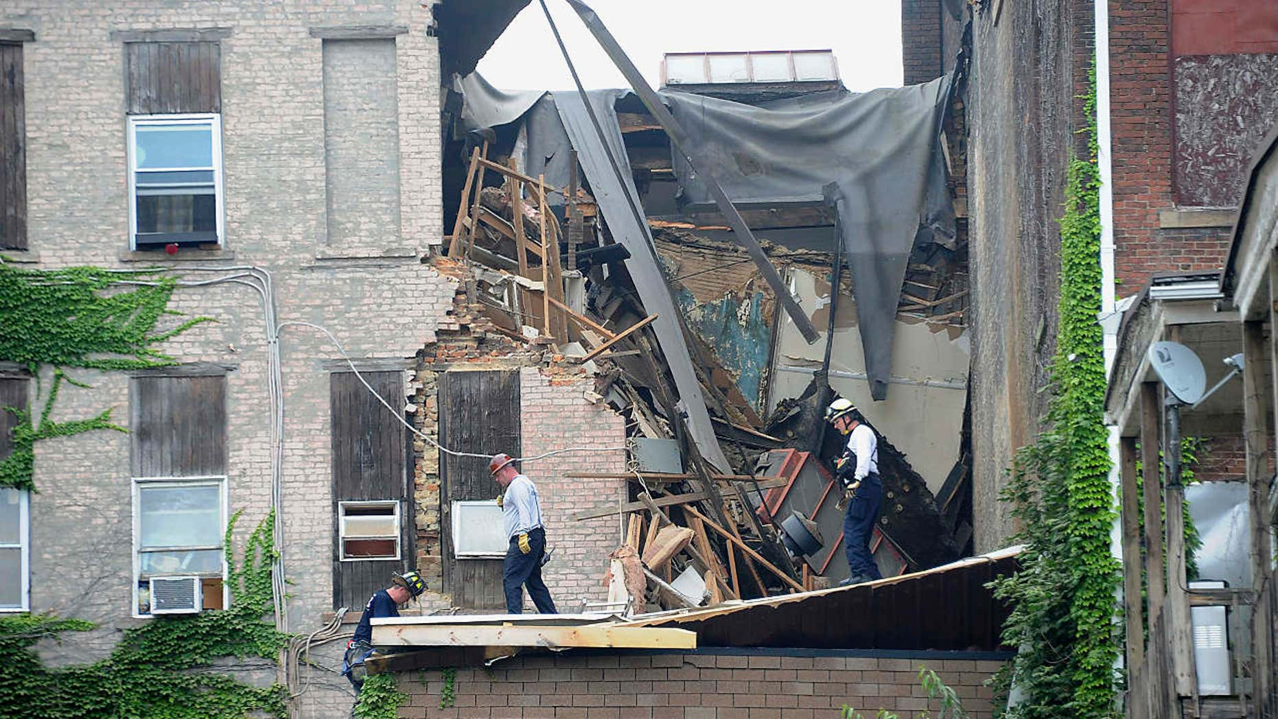 Emergency workers examine an apartment building that collapsed in Washington, Pa., Wednesday July 12, 2017.
