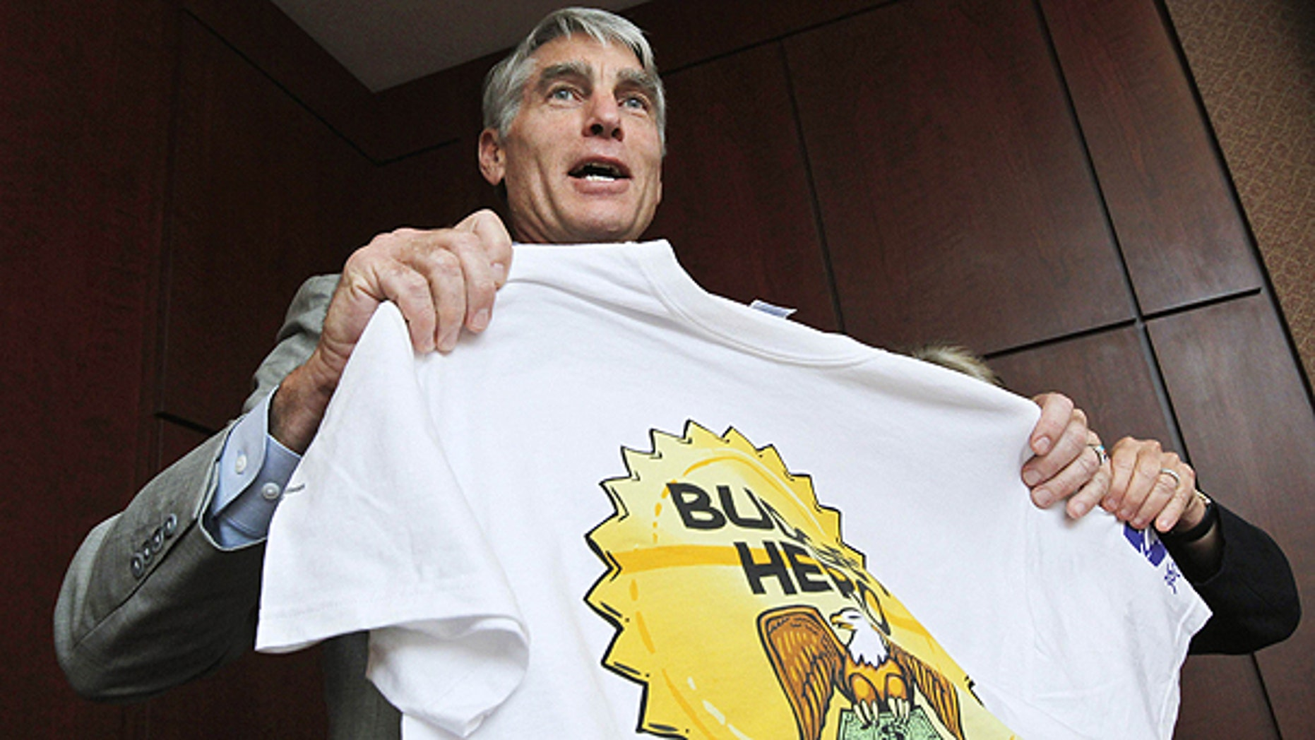 """July 13: Sen. Mark Udall, D-Colo., shows his Budget Hero shirt at the Wilson Center's re-launching of the """"Budget Game"""" on Capitol Hill in Washington."""