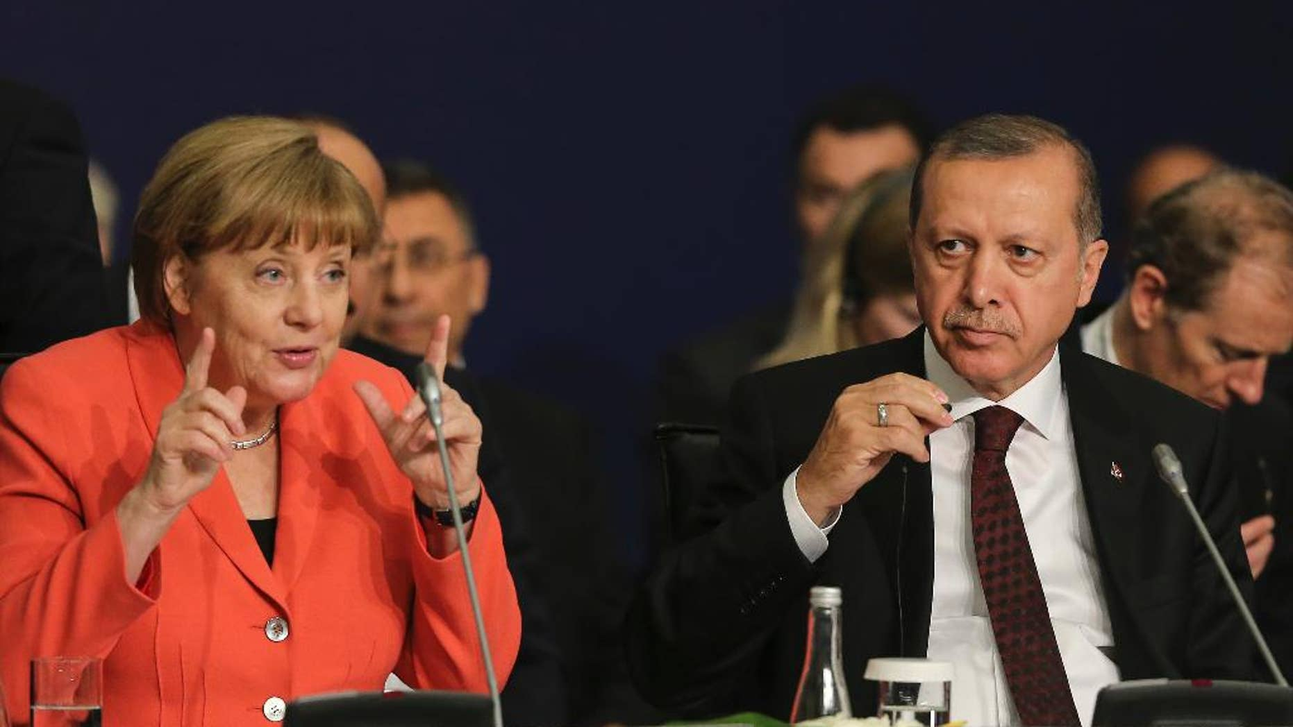 """German Chancellor Angela Merkel, left, talks as Turkey's President Recep Tayyip Erdogan listens during a roundtable meeting on """"Political Leadership to Prevent and End Conflicts"""" at the World Humanitarian Summit in Istanbul, Monday, May 23, 2016. World leaders and representatives of humanitarian organisations from across the globe converge in Istanbul on May 23-24, 2016 for the first World Humanitarian Summit, focused on how to reform a system many judge broken. (Salih Zeki Fazlioglu/Anadolu, Pool Photo via AP)"""