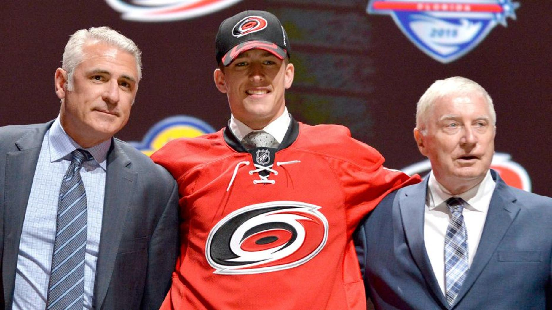 Jun 26, 2015; Sunrise, FL, USA; Noah Hanifin poses with team executives after being selected as the number five overall pick to the Carolina Hurricanes in the first round of the 2015 NHL Draft at BB&T Center. Mandatory Credit: Steve Mitchell-USA TODAY Sports