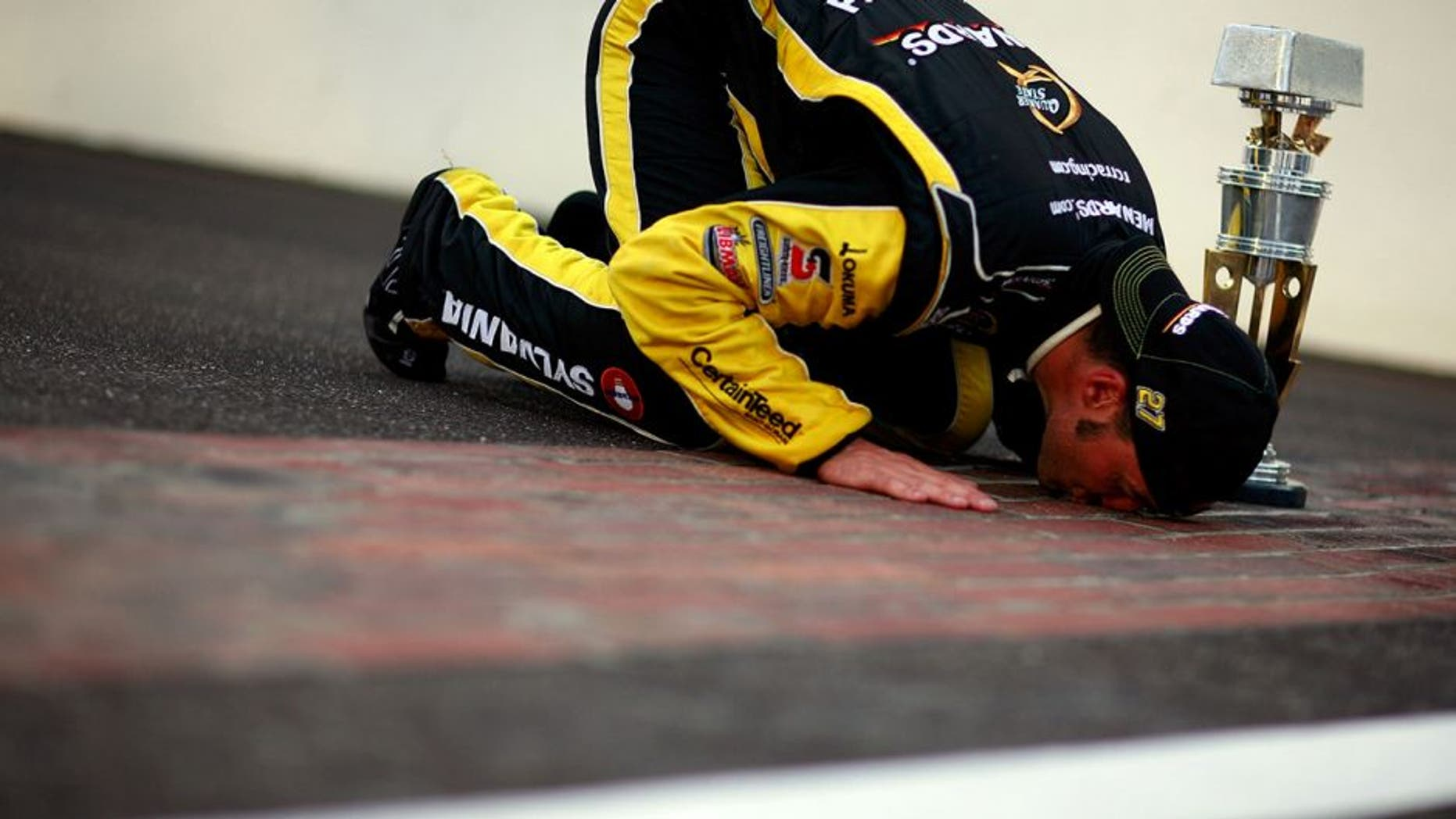 INDIANAPOLIS, IN - JULY 31: Paul Menard, driver of the #27 NIBCO/Menards Chevrolet, poses as he kisses the bricks after winning the NASCAR Sprint Cup Series Brickyard 400 at Indianapolis Motor Speedway on July 31, 2011 in Indianapolis, Indiana. (Photo by Tom Pennington/Getty Images for NASCAR)
