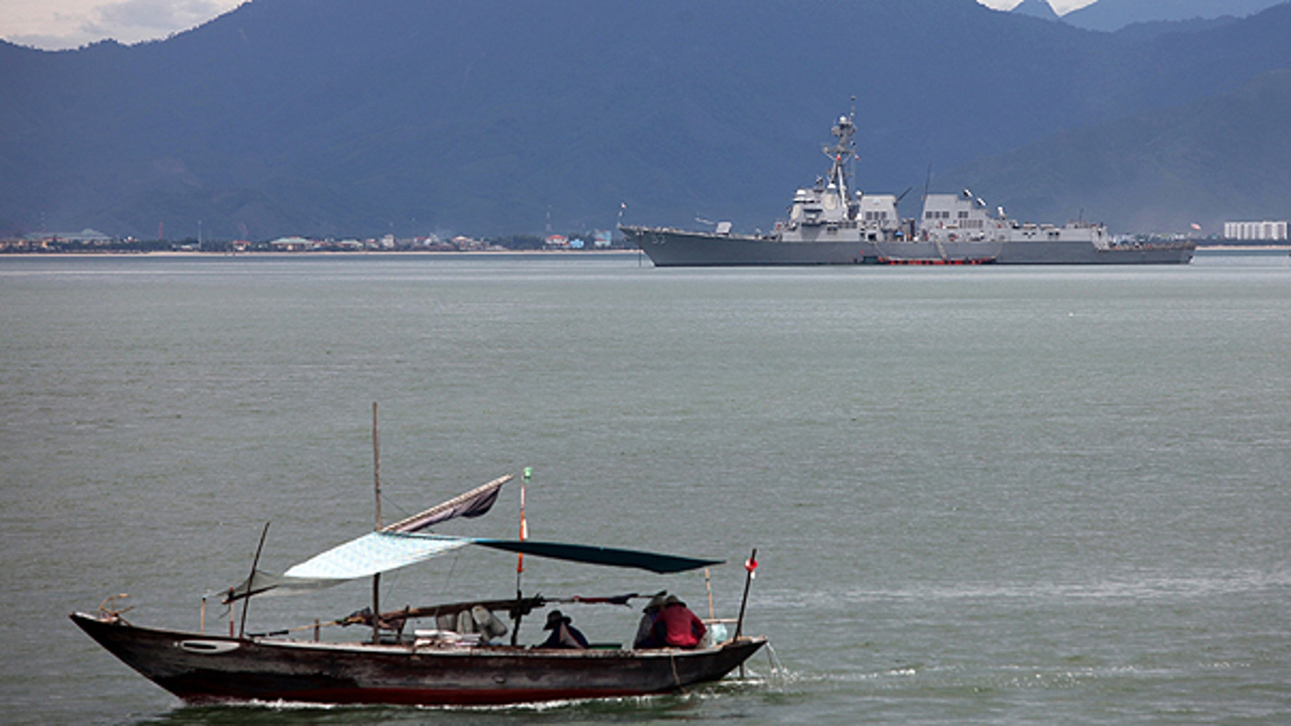 July 15: A Vietnamese fisher boat passes near the guided missile destroyer USS Chung-Hoon which is anchored on the background during a port visit for the naval exchange activities of the guided missile destroyers USS Chung-Hoon and USS Preble, as well as the rescue and salvage ship USNS Safeguard to Danang port, Danang province, Vietnam.