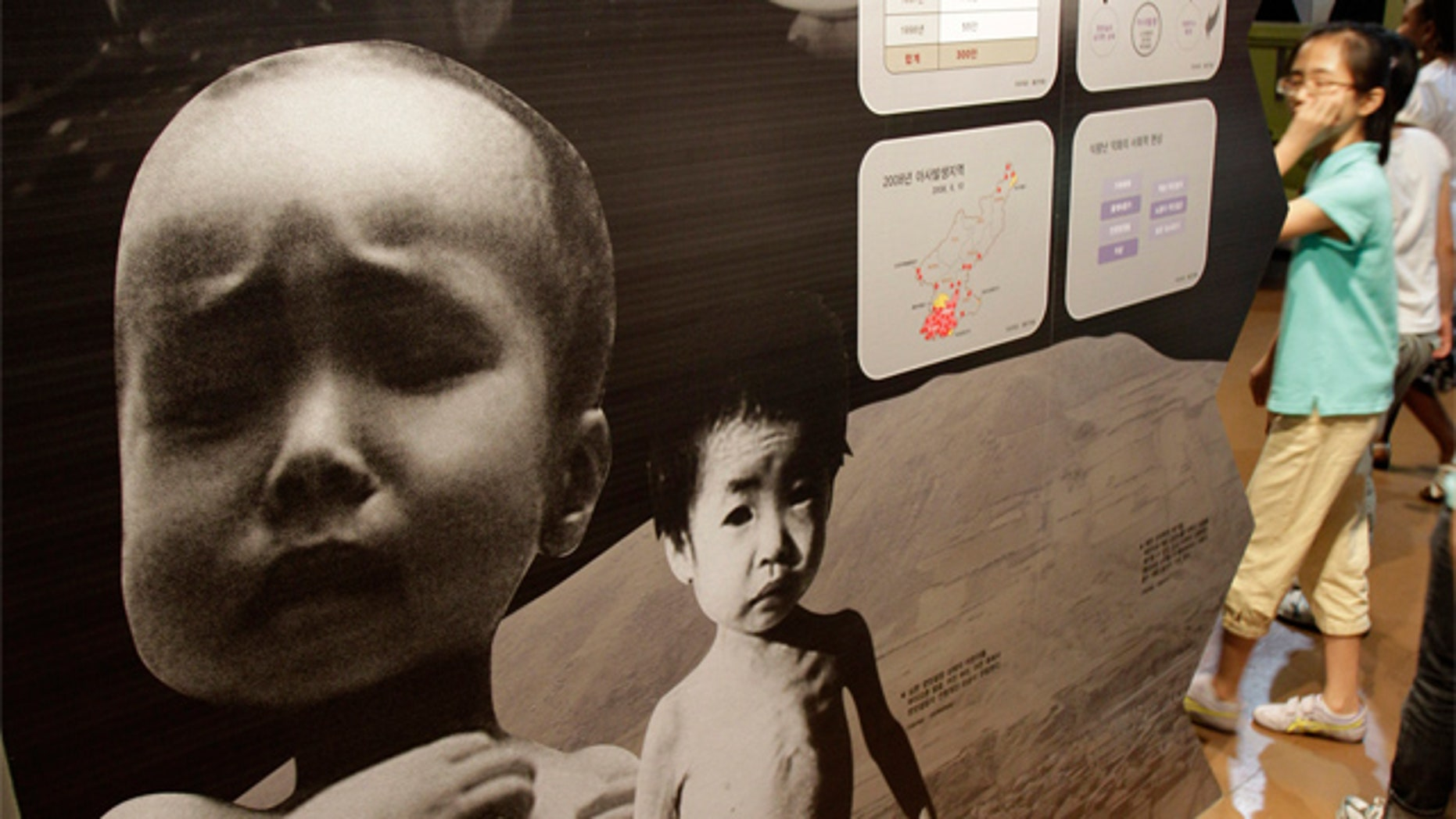 July 15: South Korean students walk by a picture showing a North Korean child suffering from famine at Korean War exhibition in Seoul, South Korea.