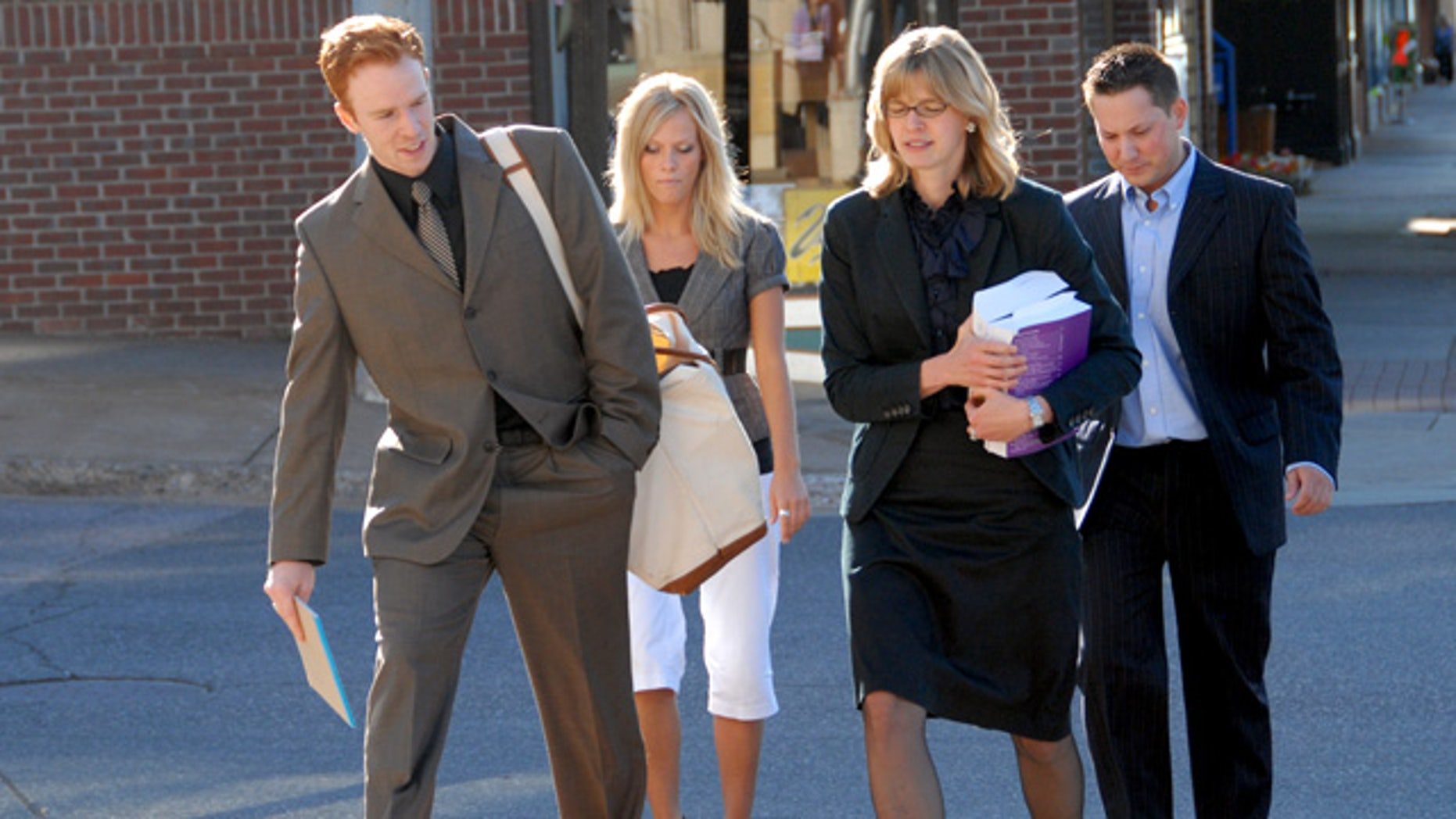 July 13: Defense attorney intern Ted Greeley, left, and lead attorney Sarah Henderson, second from right, walk with clients Allison Coss and Scott Sippola to the federal courthouse for the second day of a trial in U.S. District Court in Marquette, Mich.