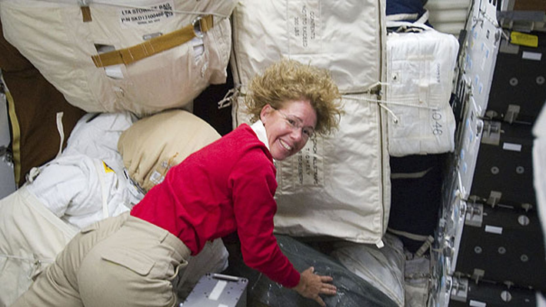 July 10: Photo provided by NASA, NASA astronaut Sandy Magnus, STS-135 mission specialist, is pictured with only a small portion of supplies and equipment on the middeck of the space shuttle Atlantis.