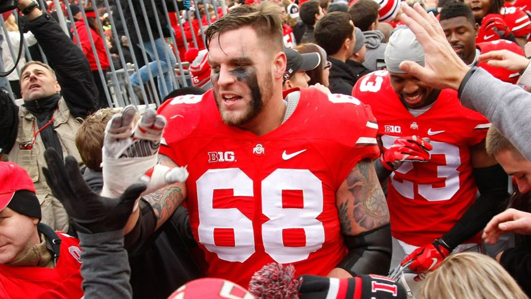 Nov 29, 2014; Columbus, OH, USA; Ohio State Buckeyes offensive lineman Taylor Decker (68) celebrates with fans following the game versus the Michigan Wolverines at Ohio Stadium. Ohio State won the game 42-28. Mandatory Credit: Joe Maiorana-USA TODAY Sports
