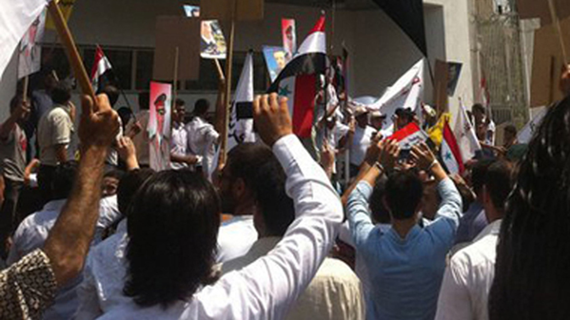 In this photo released by a Syrian news website Shukumaku, pro-Syrian President Bashar Assad protesters hang a huge Syrian flag at the entrance of the U.S. the embassy compound as they protest against the U.S. Ambassador Robert Ford after his visit to the Syrian city of Hama.
