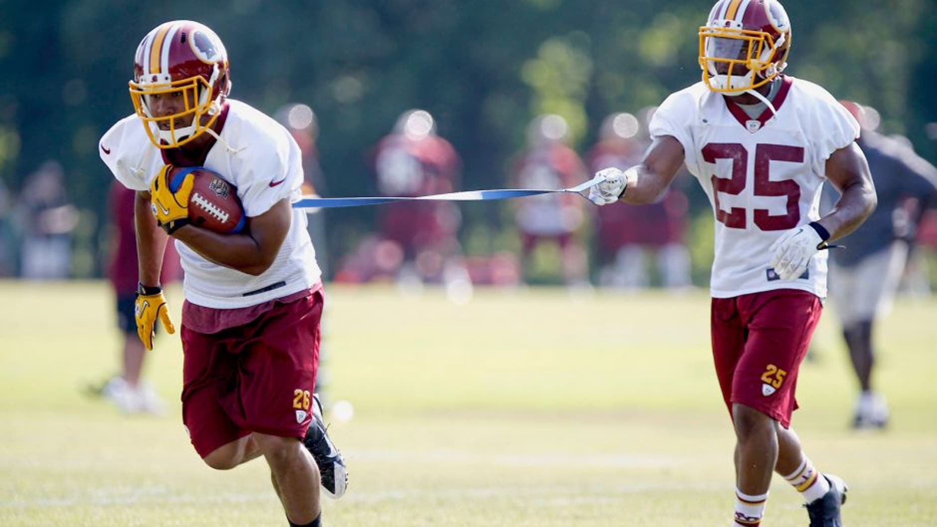 Jun 17, 2014; Ashburn, VA, USA; Washington Redskins running back Evan Royster (26) and Redskins running back Chris Thompson (25) participate in drills during minicamp at Redskins Park. Mandatory Credit: Geoff Burke-USA TODAY Sports