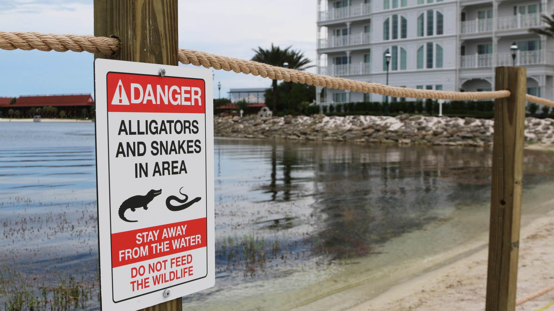 FILE - In this Friday, June, 17, 2016 file photo released by Walt Disney World Resort, a new sign is seen posted on a beach outside a hotel at a Walt Disney World resort in Lake Buena Vista, Fla., after a 2-year-old Nebraska boy killed by an alligator at Disney World.