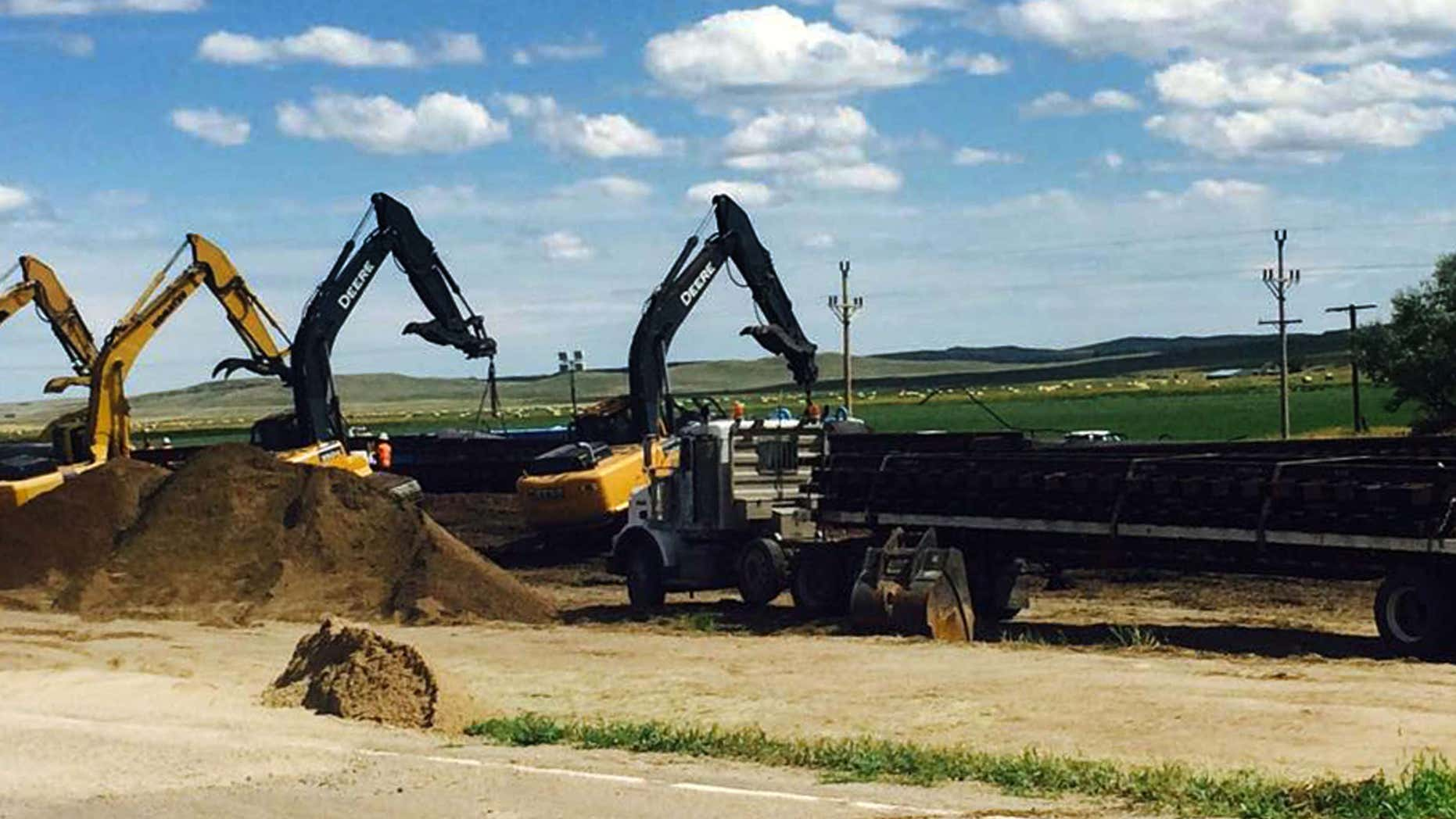 July 17, 2015: Crews with cranes attempt to raise derailed oil tanker cars near Culbertson, Mont.