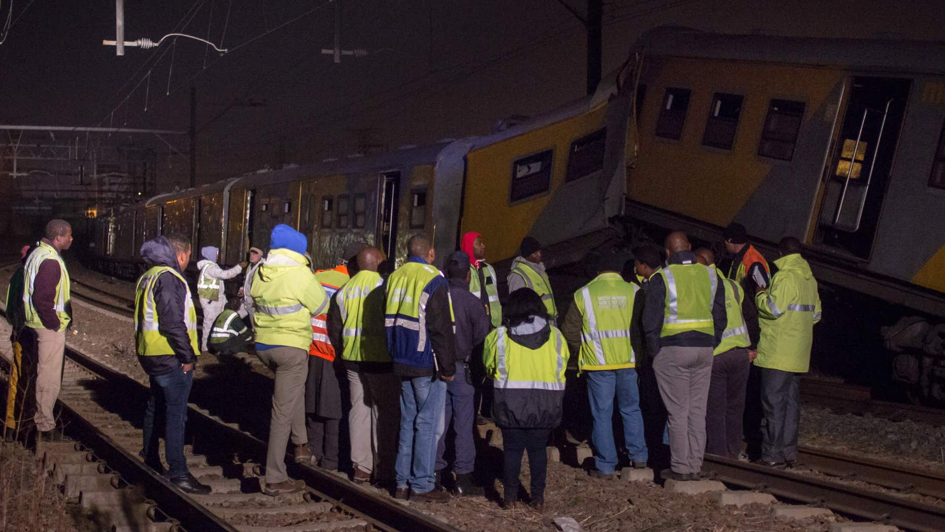 July 17, 2015: Emergency workers gather at the scene of a train collision at the Booysens train station near Johannesburg.