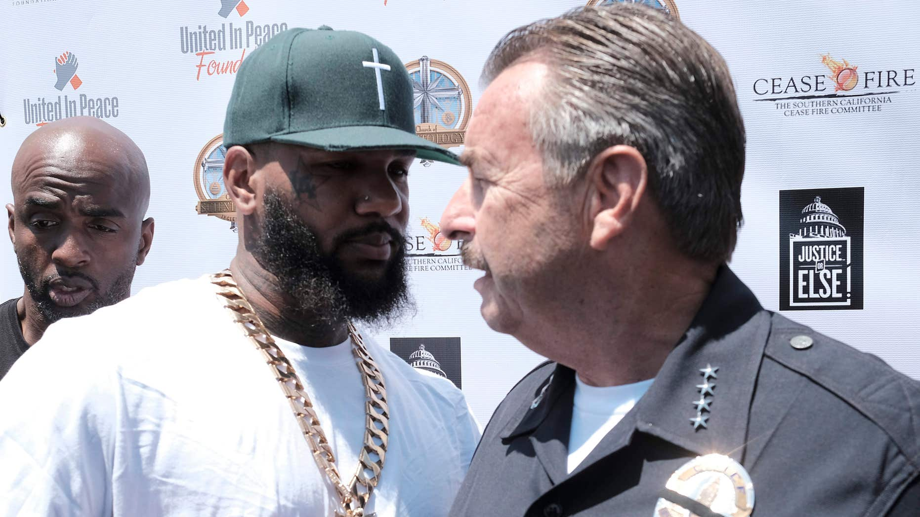 "July 17, 2016: The Game, left, shakes hands with Los Angeles Police Chief Charlie Beck during ""Time To Unite: United Hoods + Gangs Nation,"" a community summit organized by rappers The Game and Snoop Dogg, at the Church of Scientology Community Center in South Los Angeles with local gang members to discuss ways to curb violence."