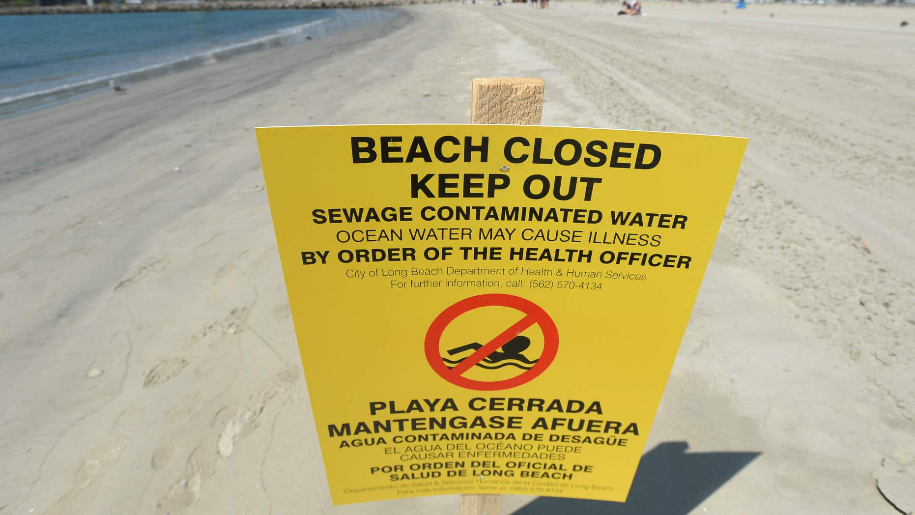 A sign is posted at Alamitos Beach warning of the dangers of sewage contaminated water Tuesday, July 19, 2016, in Long Beach, Calif.