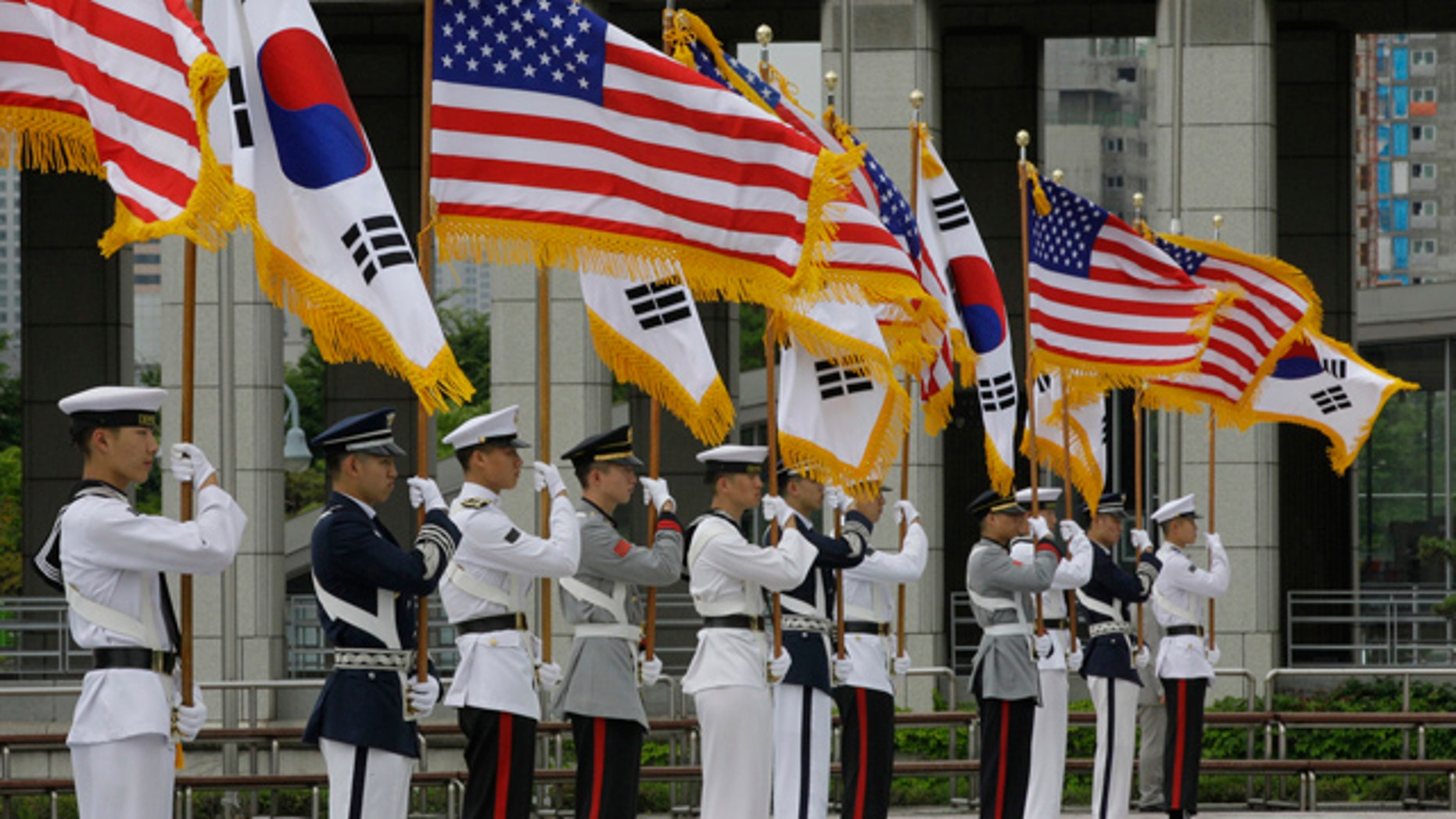 South Korean honor guard soldiers hold American and South Korean national flags during a rehearsal for the welcoming ceremony of U.S. Secretary of State Hillary Rodham Clinton and Defense Secretary Robert Gates in Seoul, South Korea, Tuesday, July 20, 2010. Gates, who arrived on Monday, will be joined by Clinton on Wednesday for high-profile security talks with their South Korean colleagues, a meeting meant to underscore Washington's firm alliance with Seoul as the two nations plan military exercises in a message of deterrence to North Korea. (AP Photo/ Lee Jin-man)