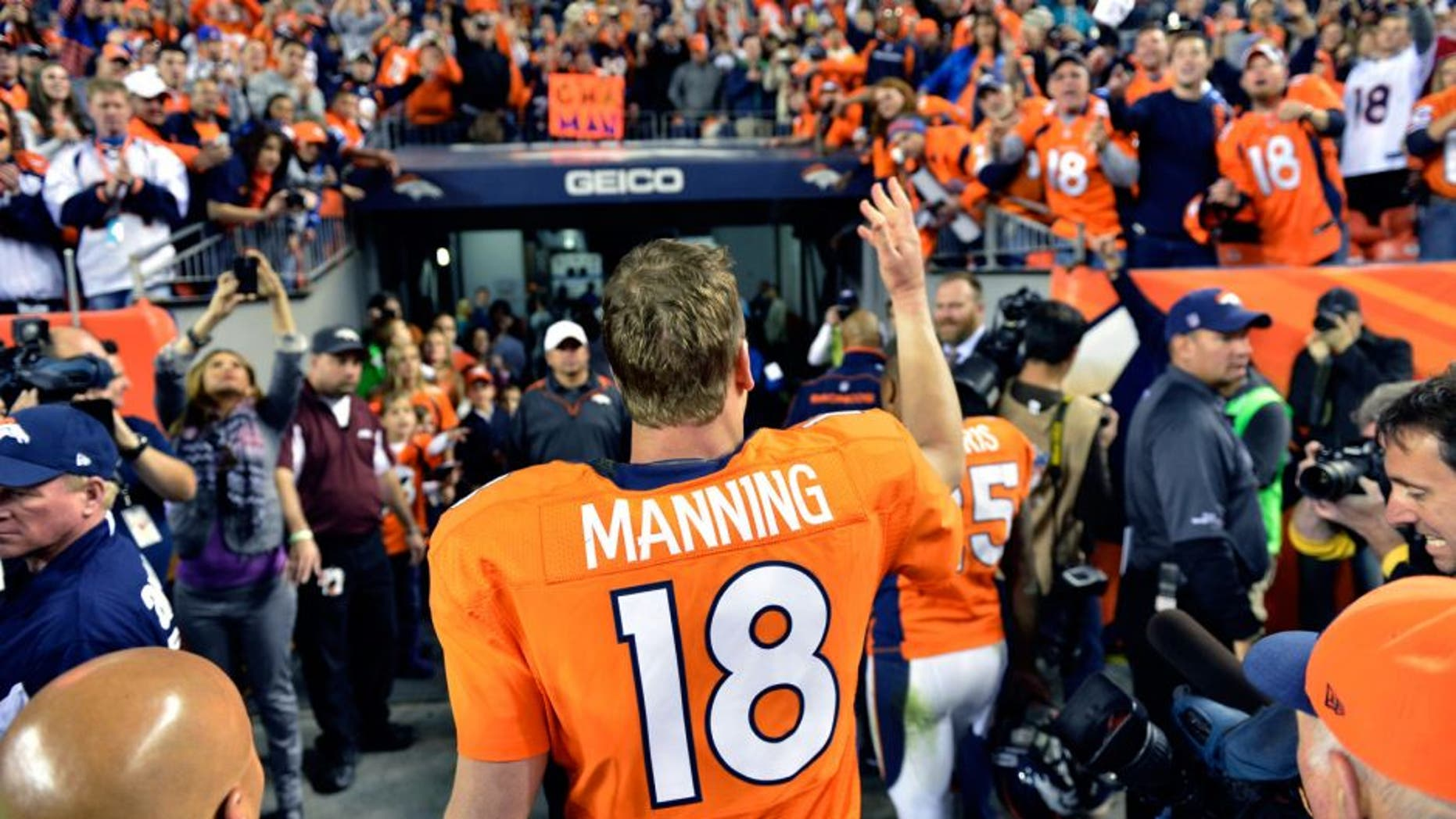 Dec 2 2012; Denver, CO, USA; Denver Broncos quarterback Peyton Manning (18) tosses a piece of equipment to the fans following the win over the Tampa Bay Buccaneers at Sports Authority Field. The Broncos defeated the Buccaneers 31-23. Mandatory Credit: Ron Chenoy-USA TODAY Sports