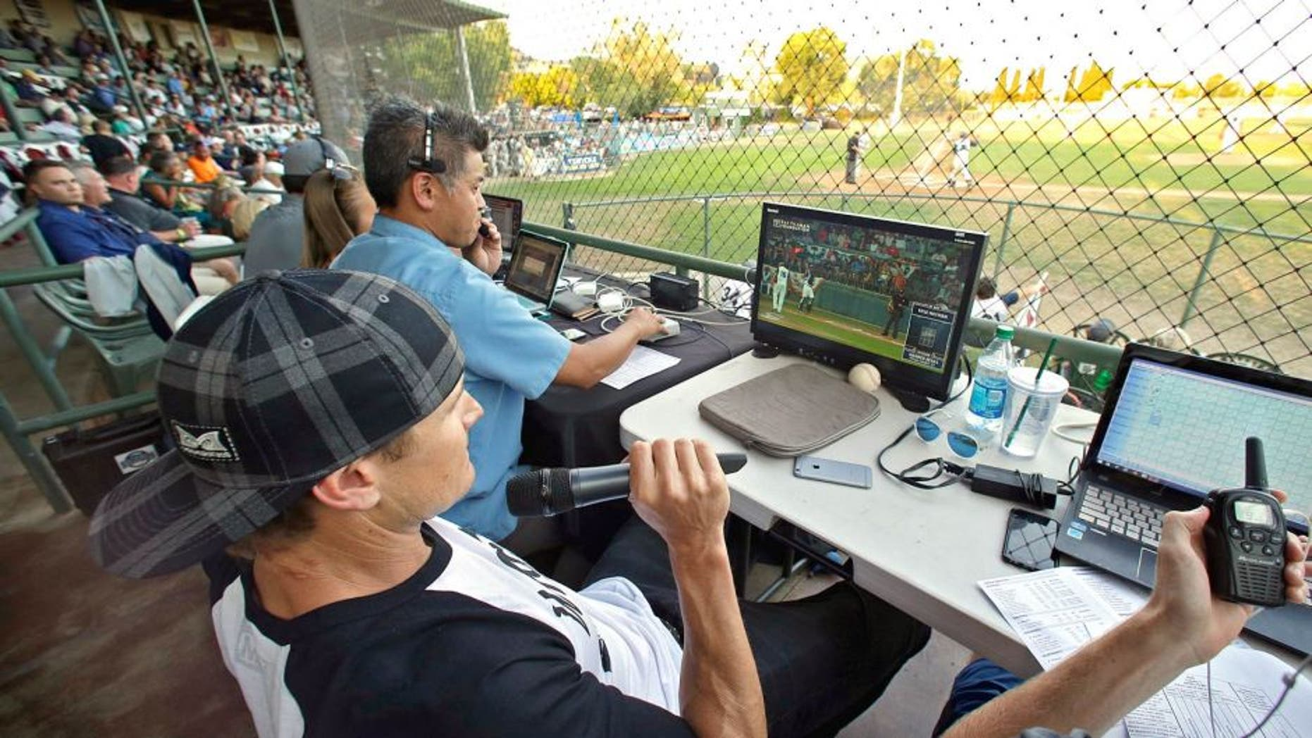 Former major league outfielder Eric Byrnes uses a computerized video system to call balls and strikes at an independent minor league baseball game between the San Rafael Pacifics and Vallejo Admirals Tuesday, July 28, 2015, in San Rafael, Calif. On Tuesday night, the computer system stood in for pitch calls in what is considered to be the first professional game without the umpire making those decisions. A full umpiring crew will be there for everything else. (AP Photo/Eric Risberg)