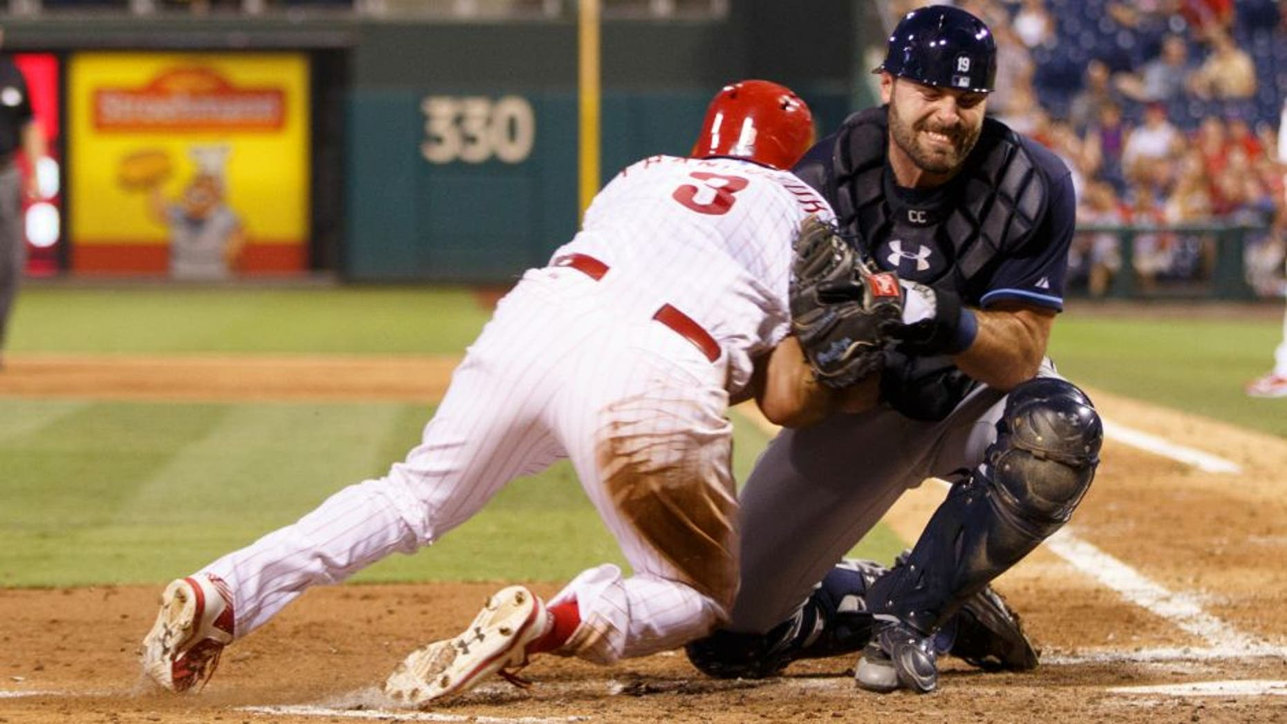 Tampa Bay Rays catcher Curt Casali, right, takes the hit from Philadelphia Phillies' Jeff Francoeur, left, as Francoeur is out at home during the fifth inning of a baseball game, Monday, July 20, 2015, in Philadelphia. (AP Photo/Chris Szagola)