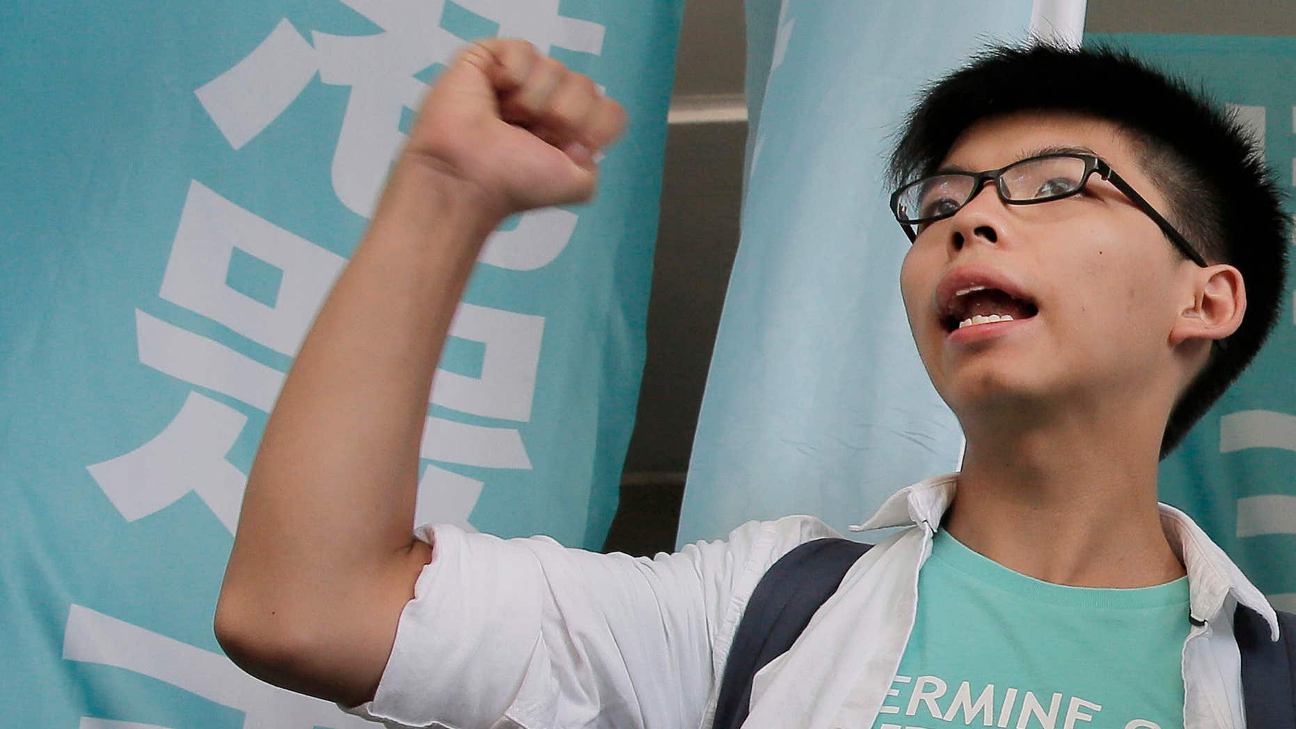 July 21, 2016: Teen protest leader Joshua Wong shouts slogans outside a magistrate's court in Hong Kong.
