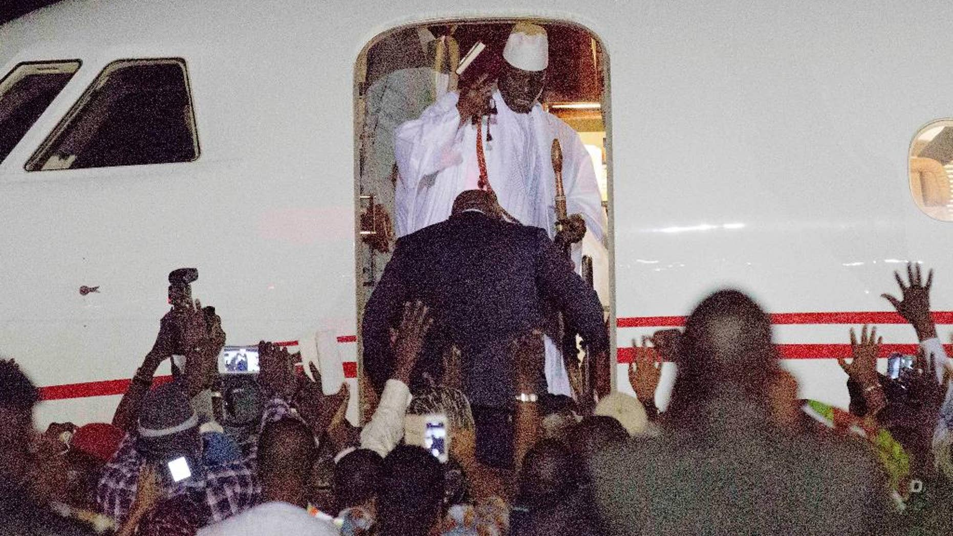"""FILE - In this file photo dated Saturday Jan. 21, 2017, Gambia's defeated leader Yahya Jammeh, top wearing white, waves to supporters as he goes into exile from Gambia's capital Banjul airport. Jammeh fiercely denounced homosexuality and warned gay people to leave the country with threats to """"cut of the head"""" of any who remained, so Jammeh's departure """"is a great relief for the population, and especially the LGBT population who were often martyred under his rule,"""" said Lambert Lamba, a leading gay rights activist in Cameroon. (AP Photo/Jerome Delay, FILE)"""