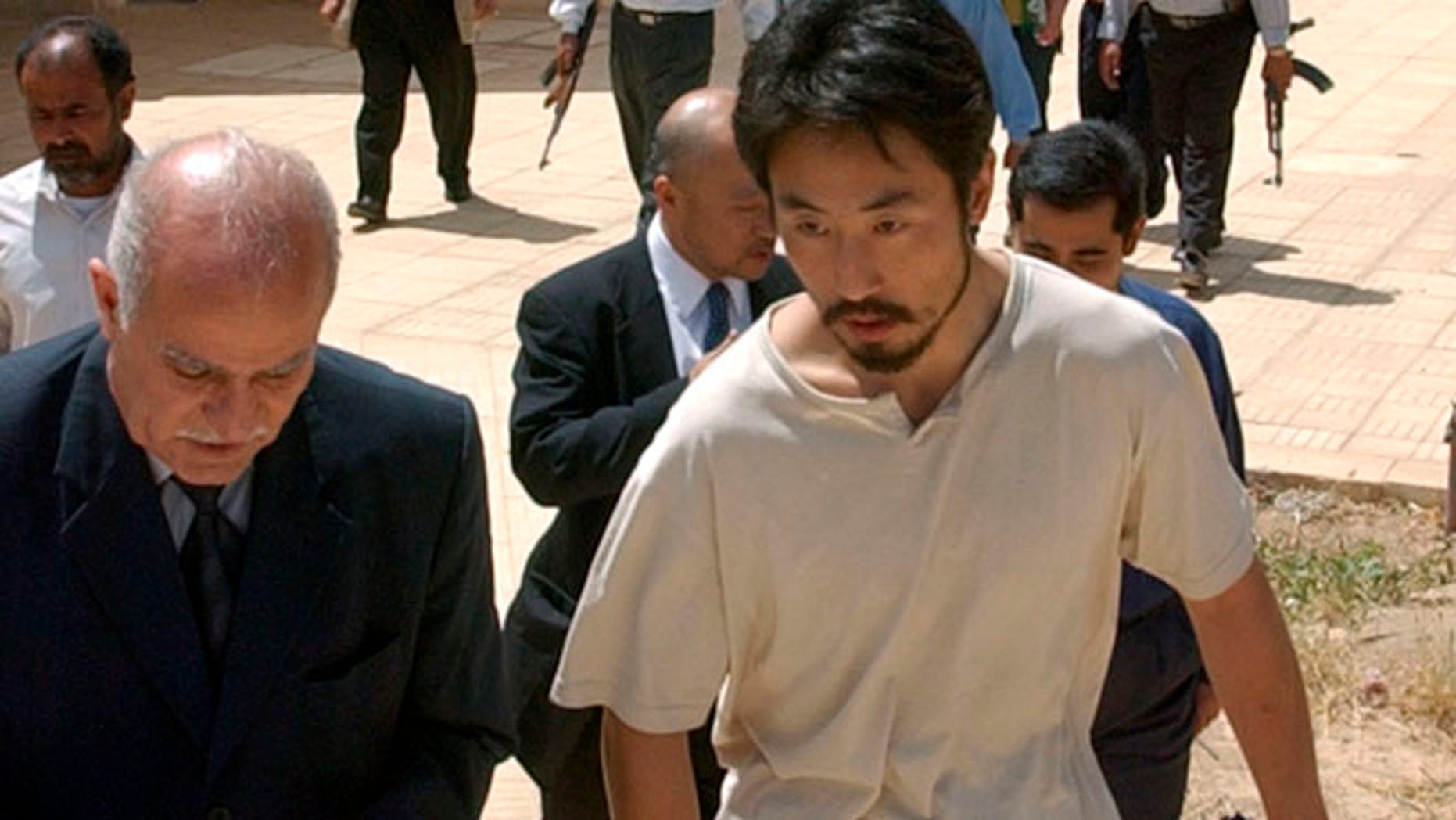 April 17, 2004: Japanese freelance journalist Jumpei Yasuda, right, is escorted after being released at Umm Al-Qura mosque in Baghdad, Iraq.  Worries are growing about the whereabouts of the freelance Japanese journalist, last heard from late June, 2015,  in Syria.