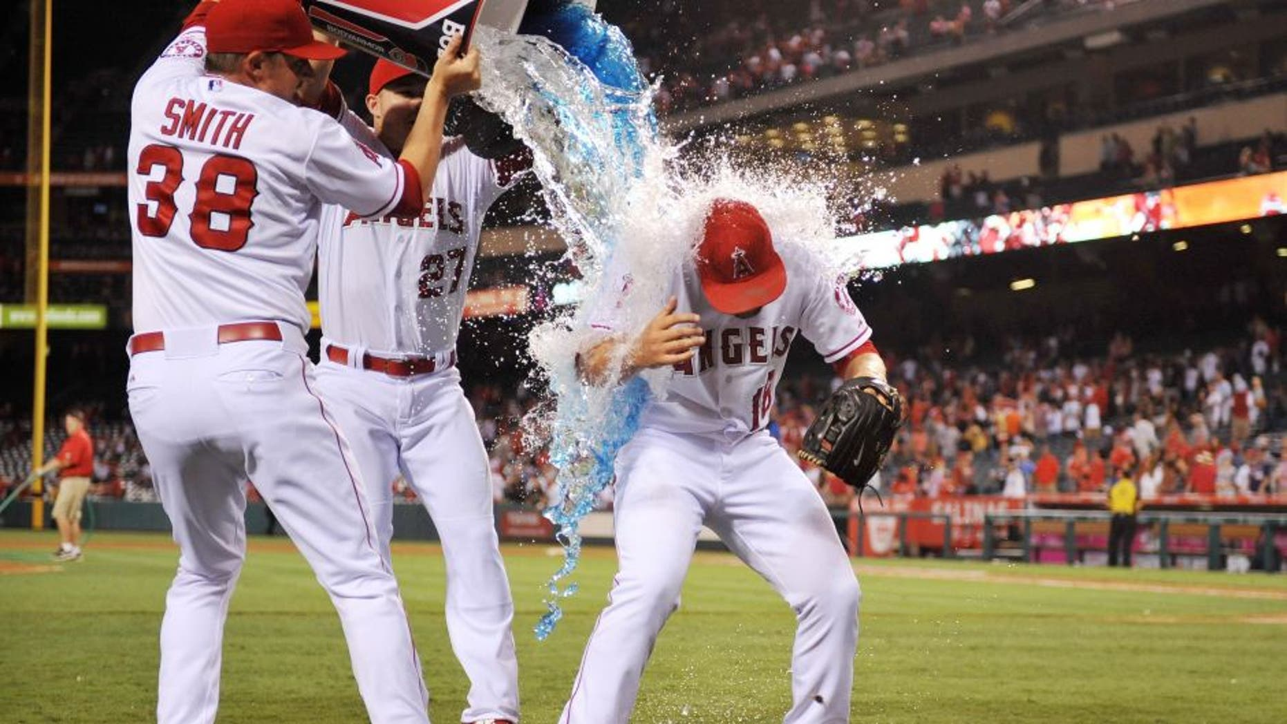 July 22, 2015; Anaheim, CA, USA; Los Angeles Angels relief pitcher Joe Smith (38) and center fielder Mike Trout (27) pour sport drink on relief pitcher Huston Street (16) in celebration of his 300th career save against the Minnesota Twins at Angel Stadium of Anaheim. Mandatory Credit: Gary A. Vasquez-USA TODAY Sports